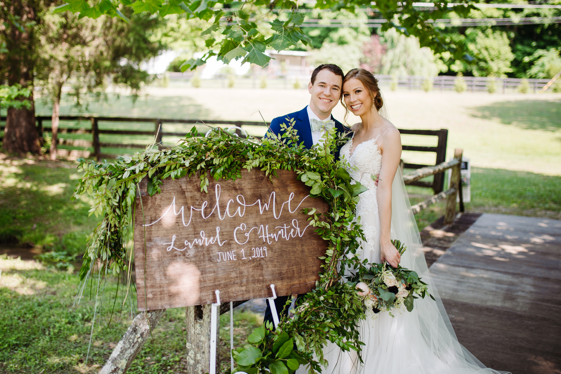 bride and groom with their hand-lettered welcome sign at a stables at strawberry creek wedding in Knoxville, tennessee