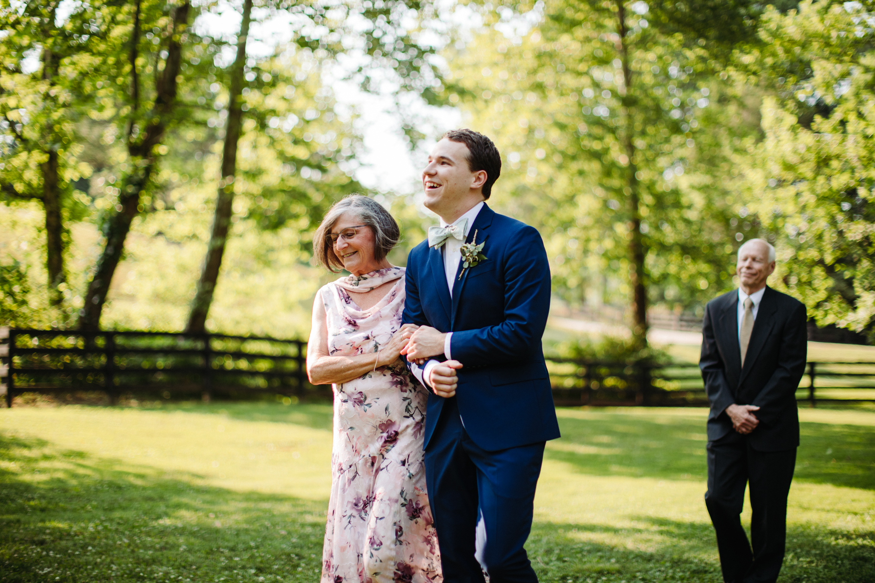Groom walks his mother down the aisle at a stables at strawberry creek wedding in knoxville, tennessee
