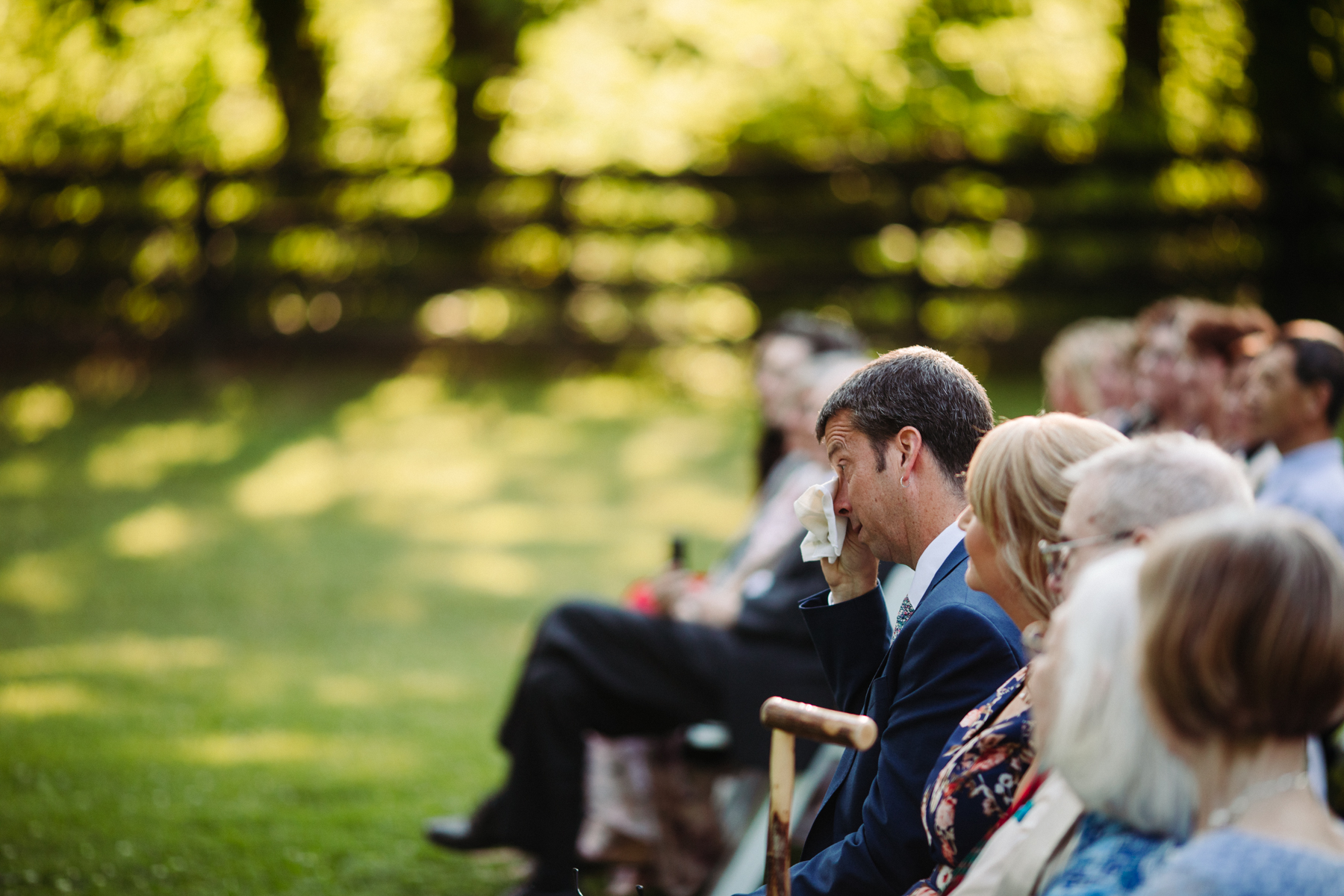 Father of the bride wipes a tear at a stables at strawberry creek wedding in knoxville, tennessee