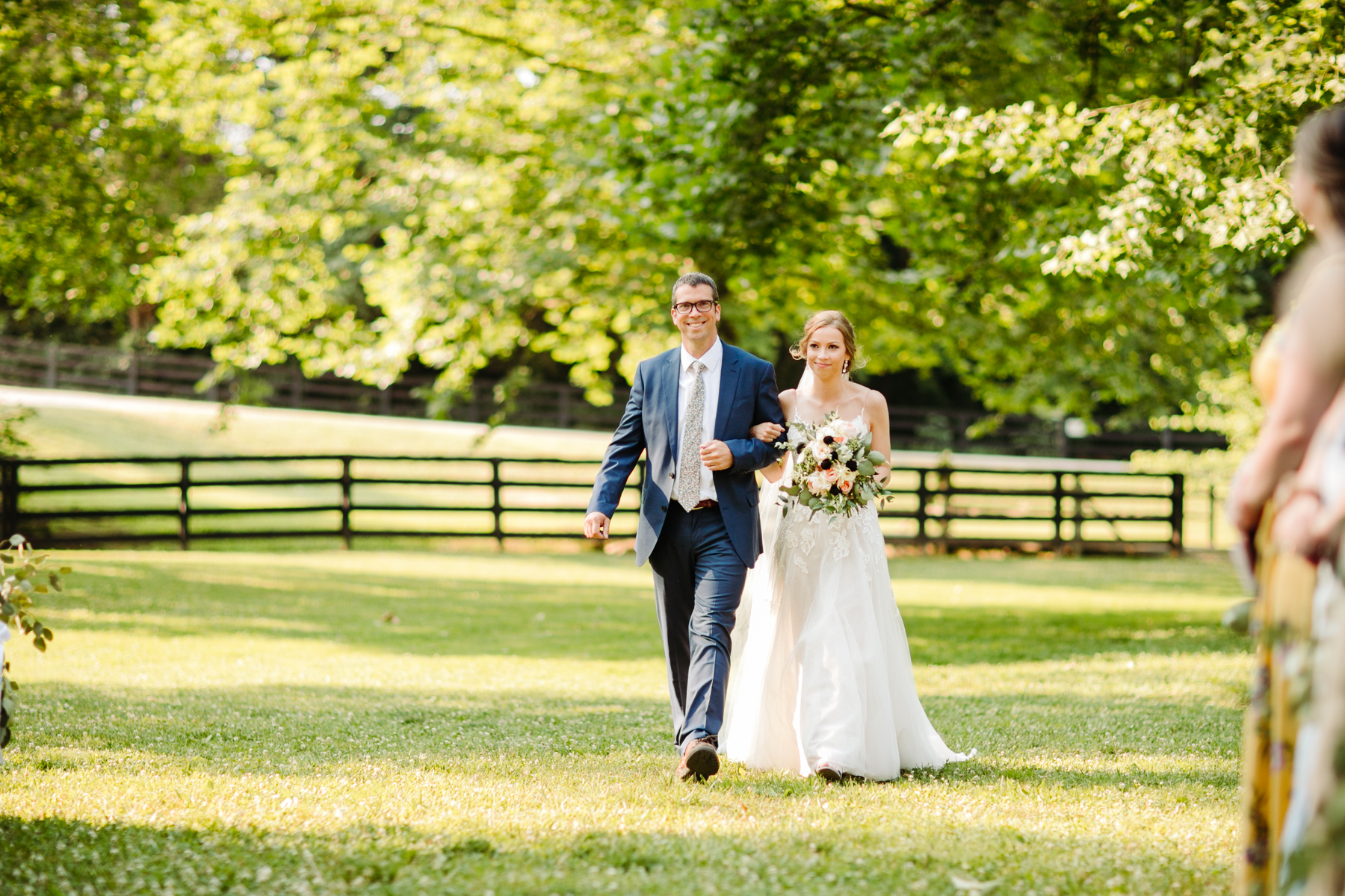 Father walking his daughter down the aisle at her stables at strawberry creek wedding in knoxville, tennessee