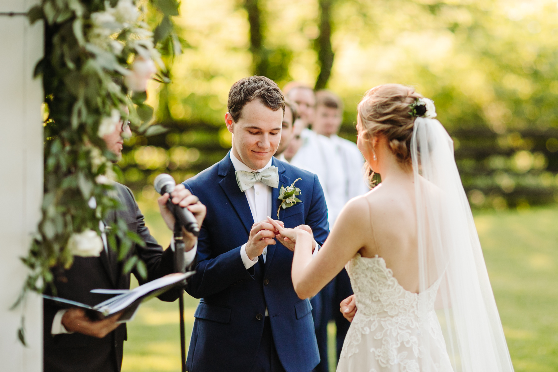 Groom puts a ring on his bride's finger at a stables at strawberry creek wedding in knoxville, tennessee