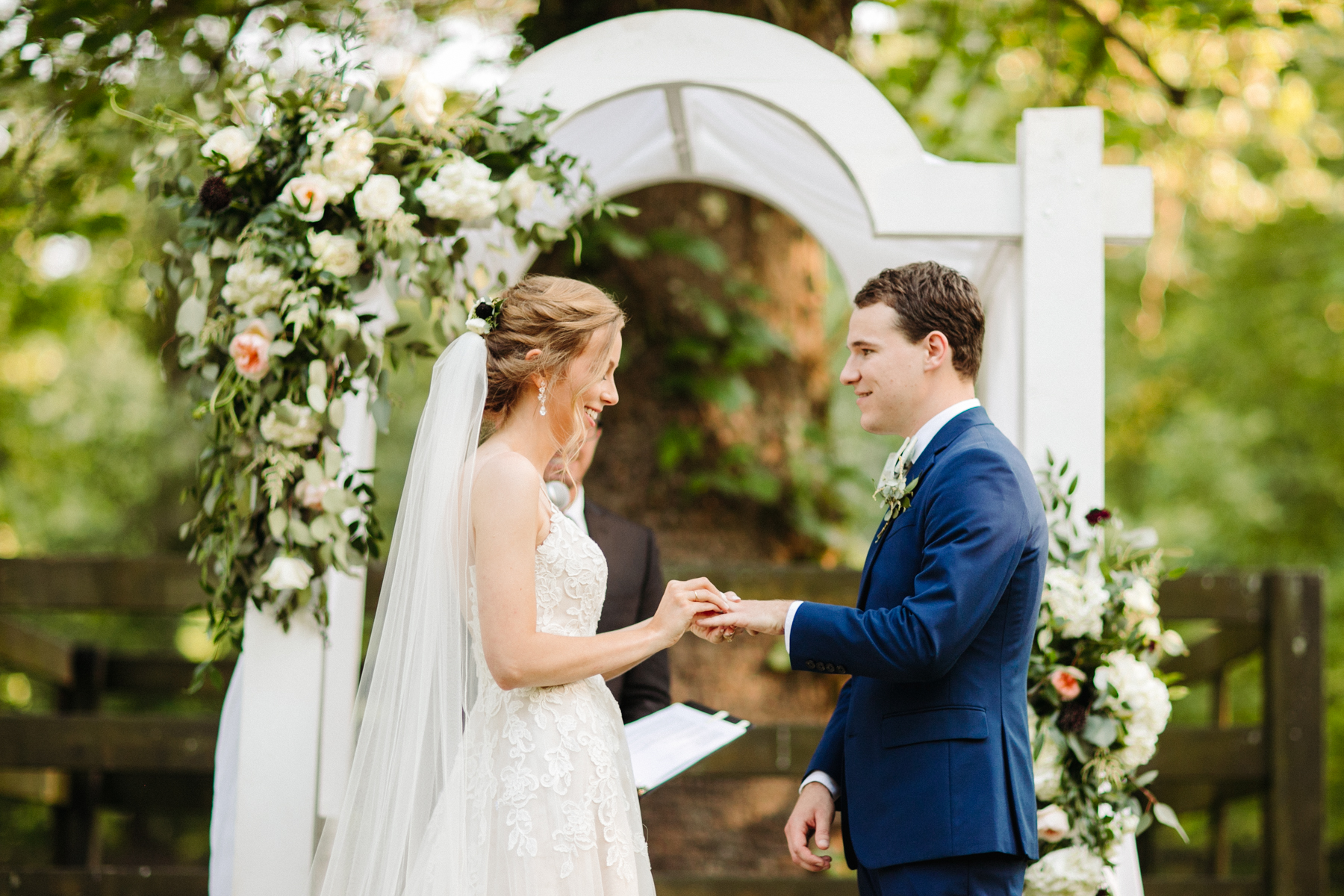bride puts a ring on her groom's finger at a stables at strawberry creek wedding in knoxville, tennessee