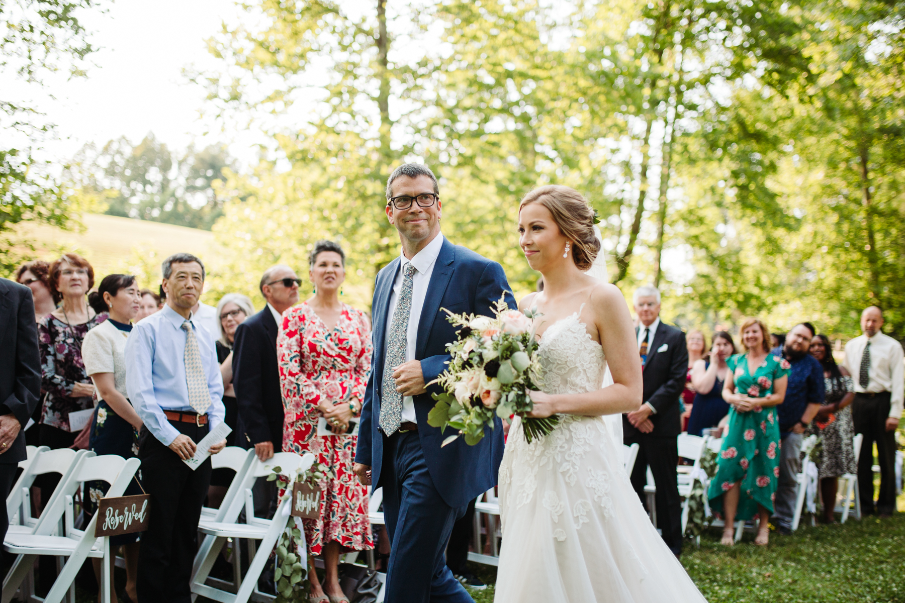 Father of the bride walking his daughter down the aisle at her stables at strawberry creek wedding in knoxville, tennessee