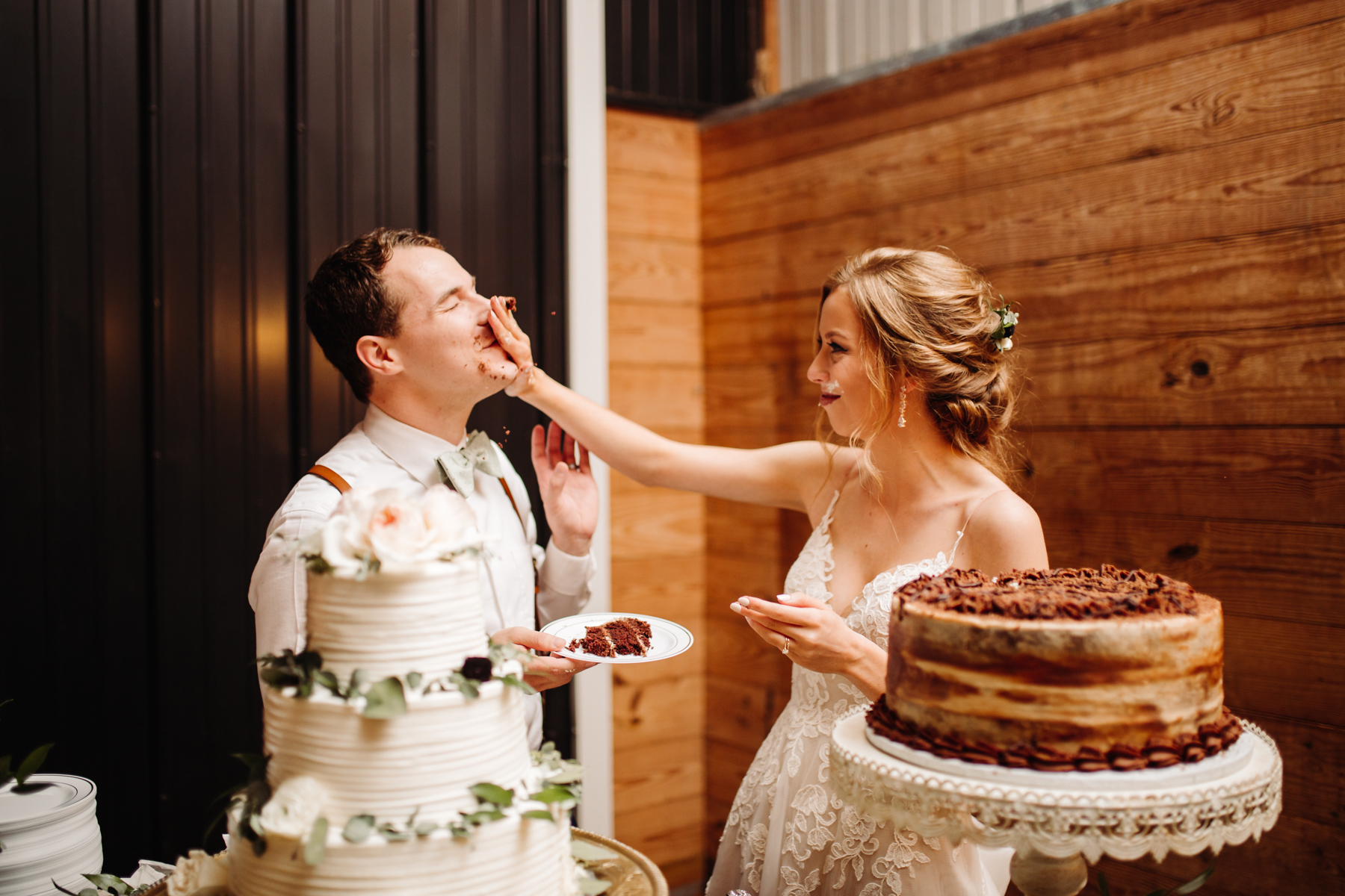 Bride smashes cake on her groom's face at their stables at strawberry creek wedding in knoxville, tennessee