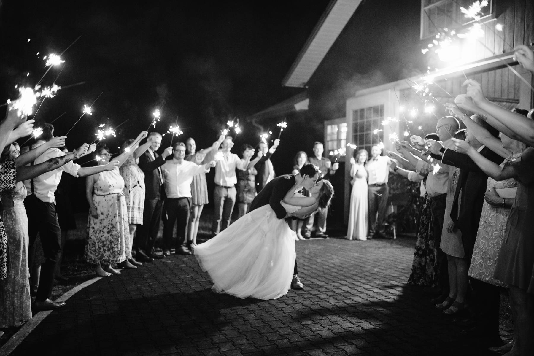 Dip kiss during a sparker exit at a stables at strawberry creek wedding in knoxville, tennessee