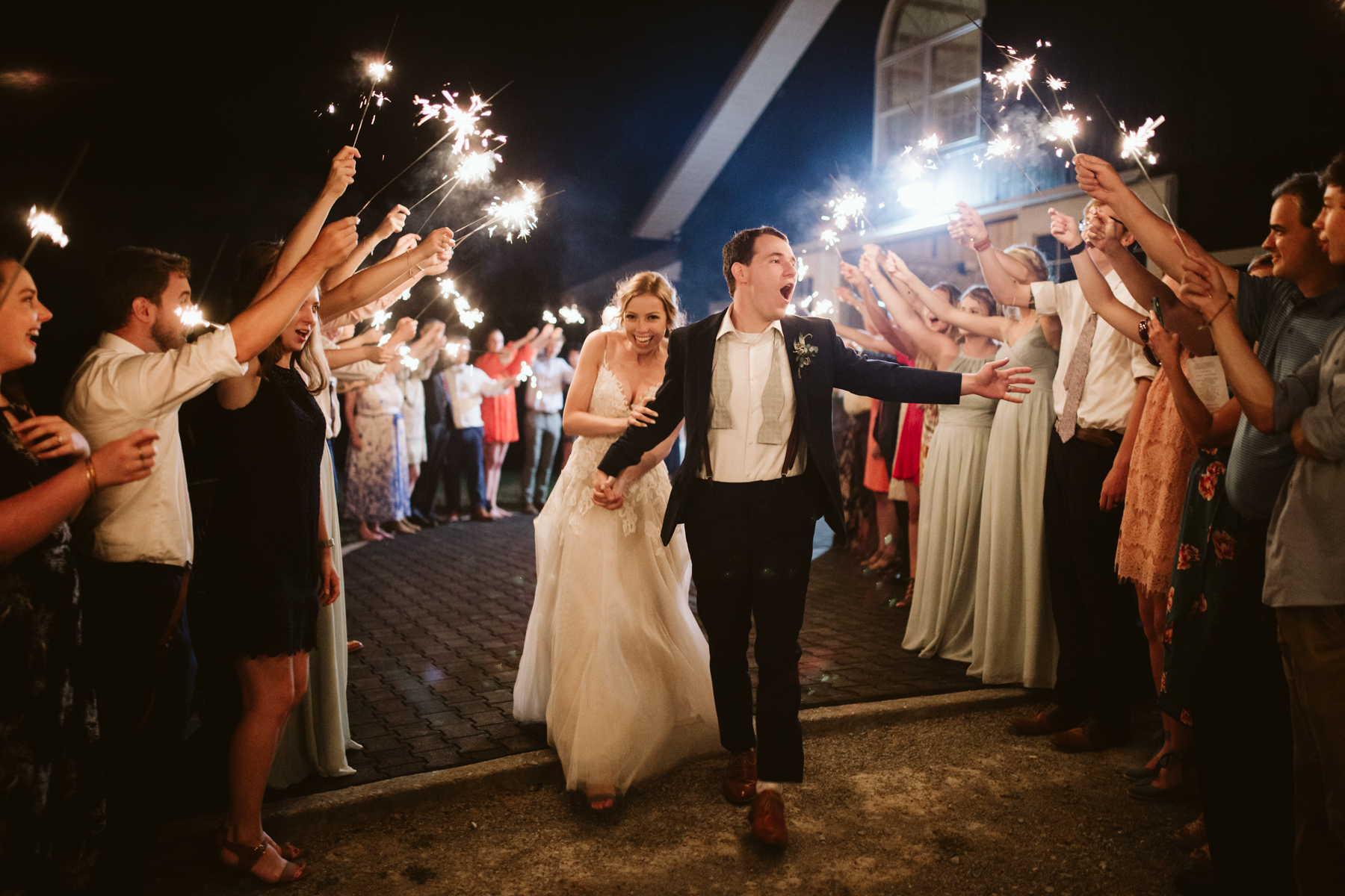Bride and groom at a lively sparkler exit after their stables at strawberry creek wedding in knoxville, tennessee
