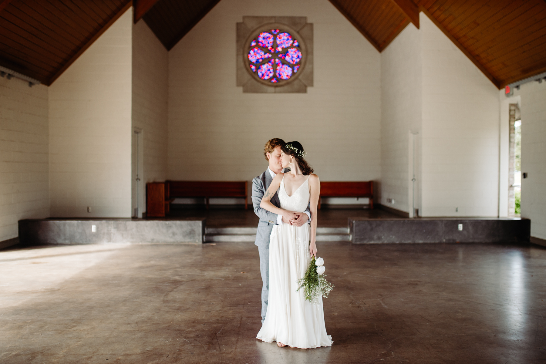 bride and groom posing inside of lakeshore chapel before their downtown knoxville wedding at redeemer church