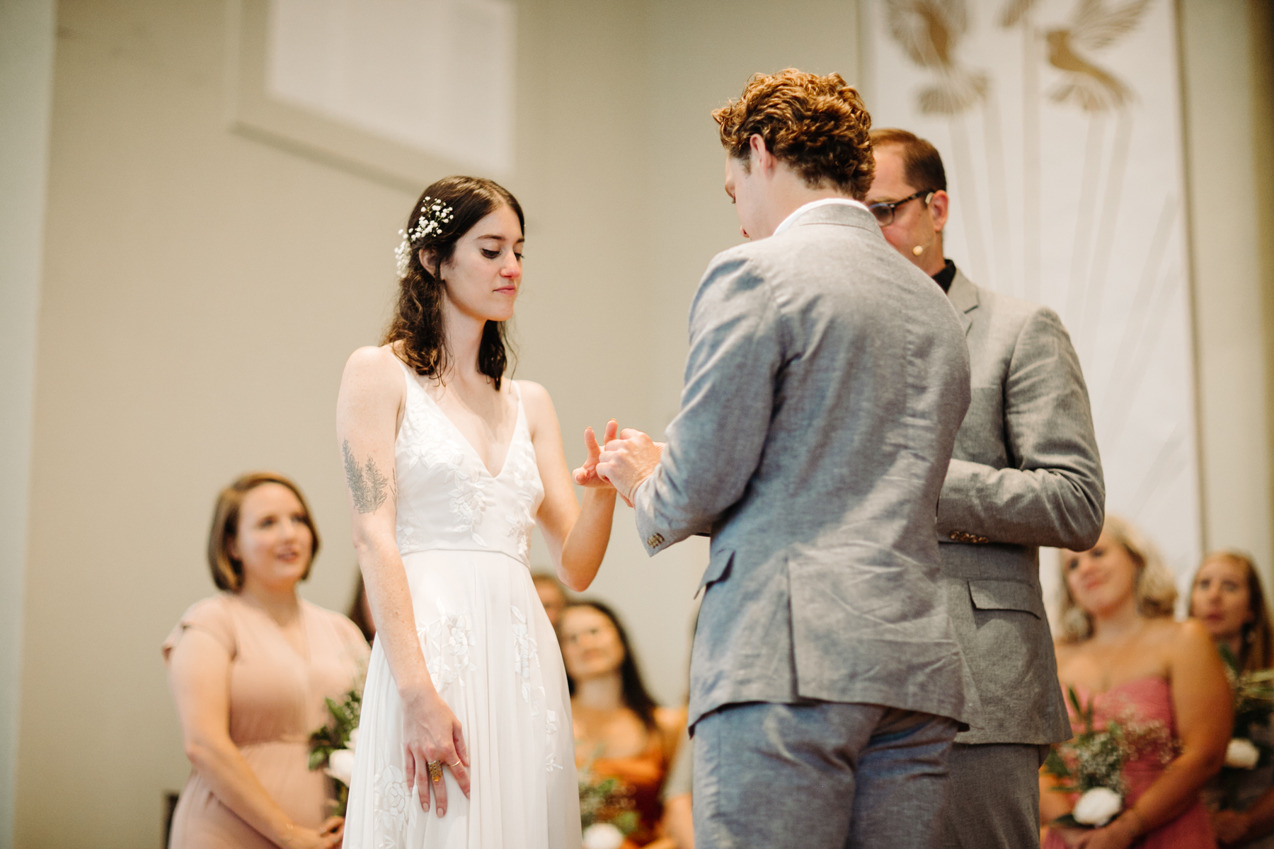 Groom putting the ring on his bride's finger at a downtown knoxville wedding at redeemer church