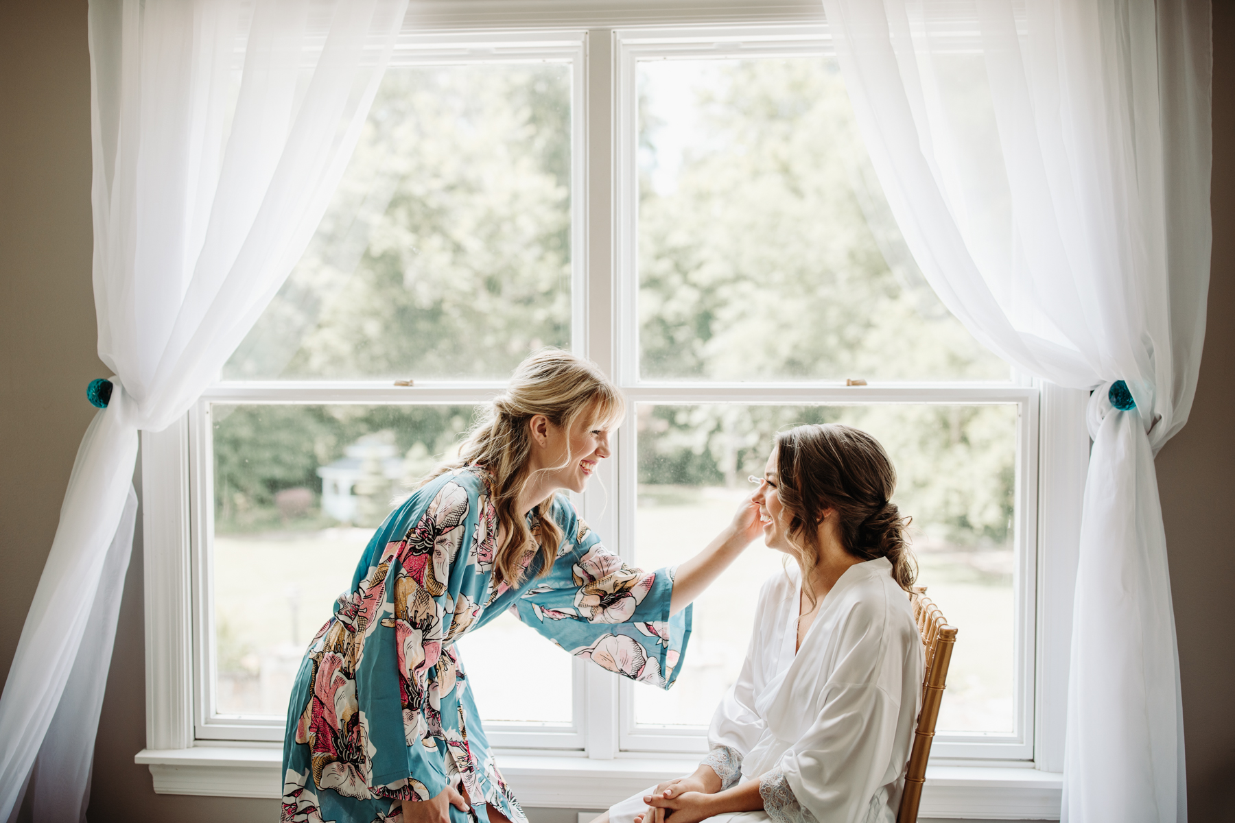 bridesmaid helping bride fix her makeup before a Sunny summer wedding at Dara's Garden in Knoxville, Tennessee