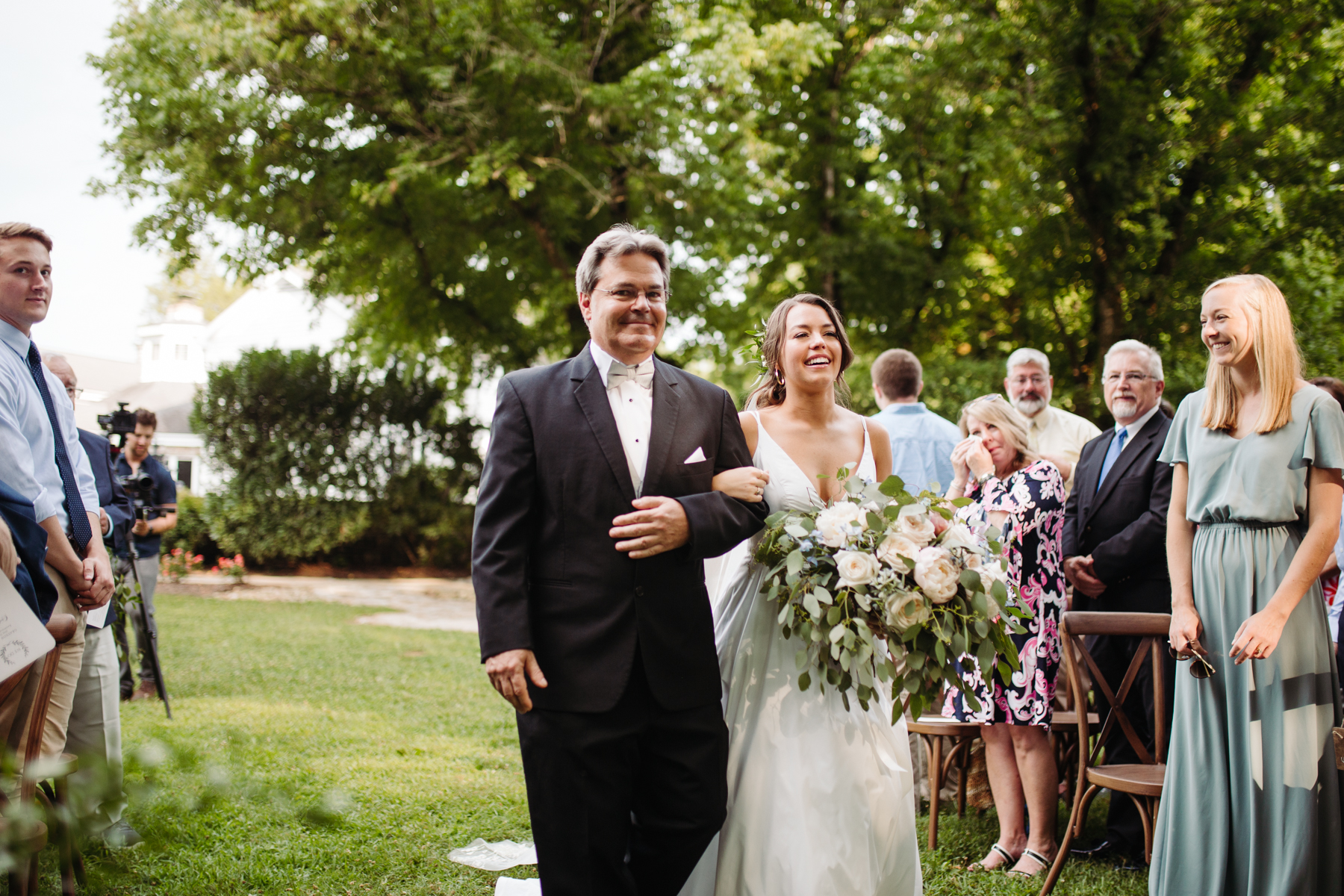Father and bride walking down the aisle at a Sunny summer wedding at Dara's Garden in Knoxville, Tennessee