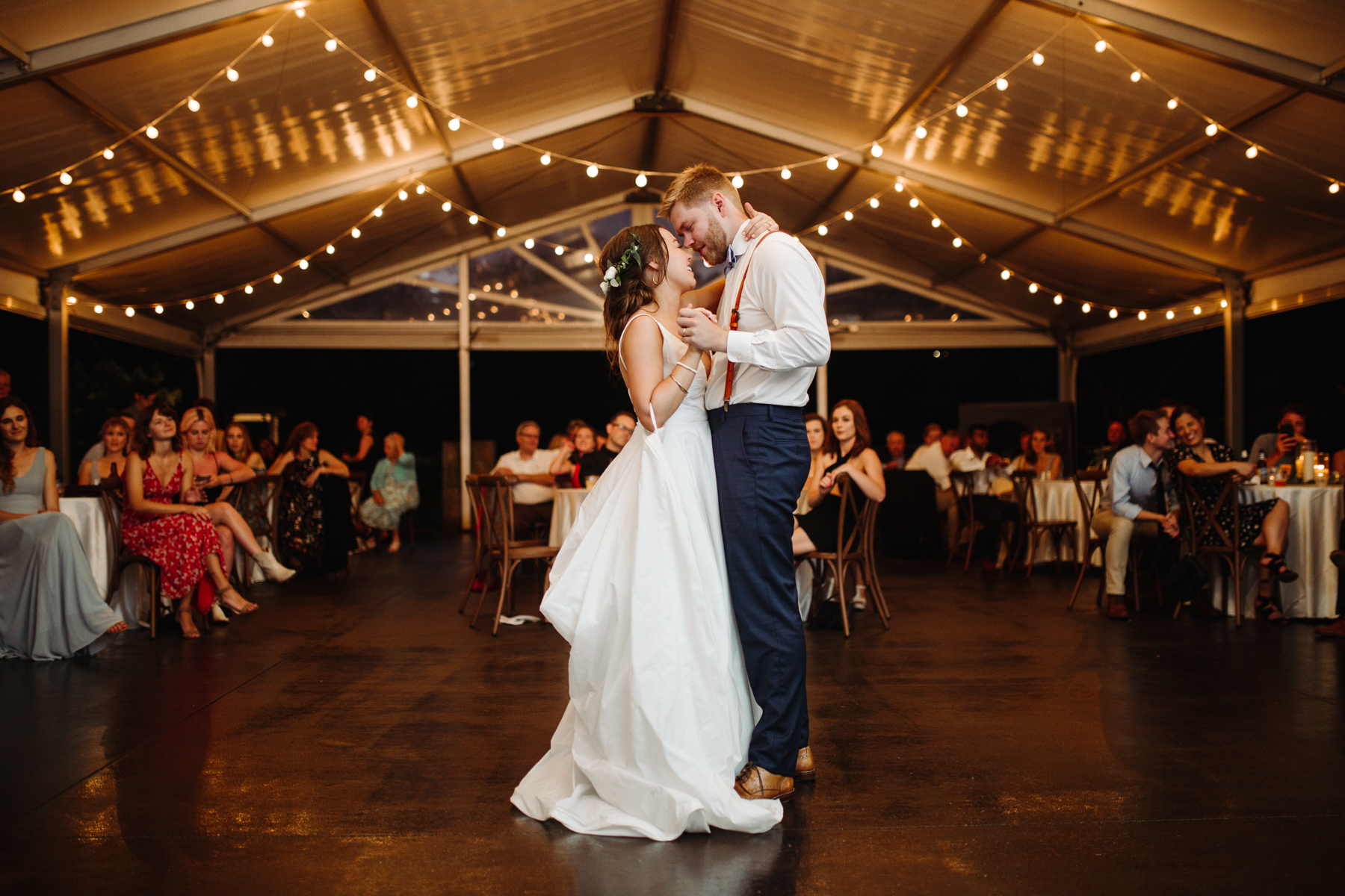 First dance under string lights at a Sunny summer wedding at Dara's Garden in Knoxville, Tennessee