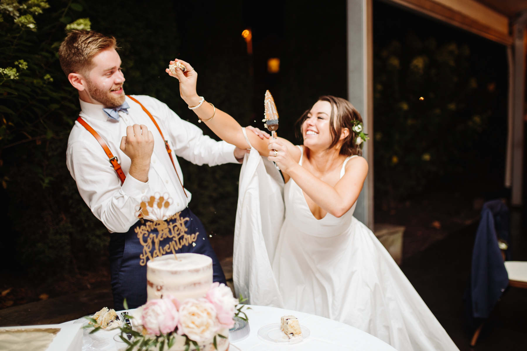 bride and groom smashing cake on each other during a reception of a Sunny summer wedding at Dara's Garden in Knoxville, Tennessee