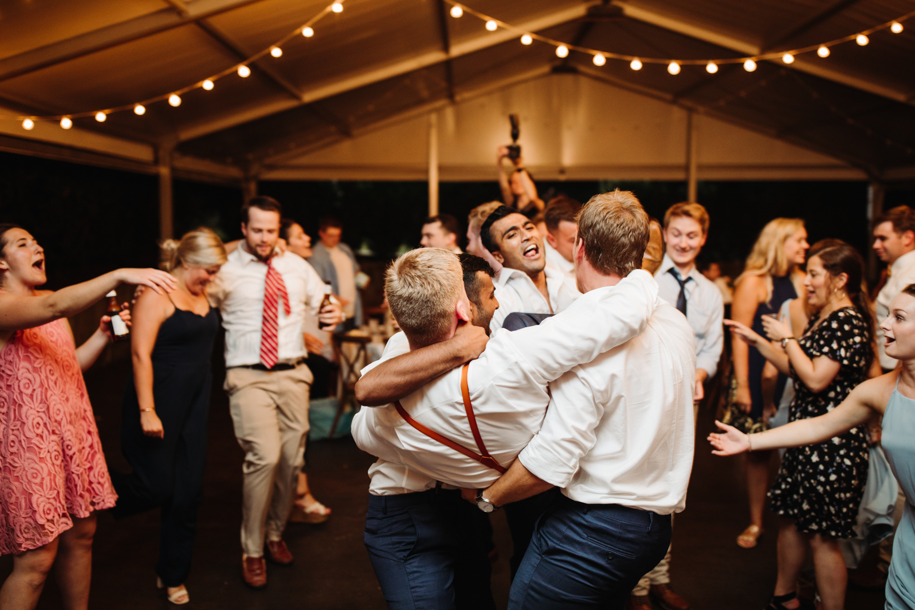 groom being carried off the dance floor at a reception of a Sunny summer wedding at Dara's Garden in Knoxville, Tennessee