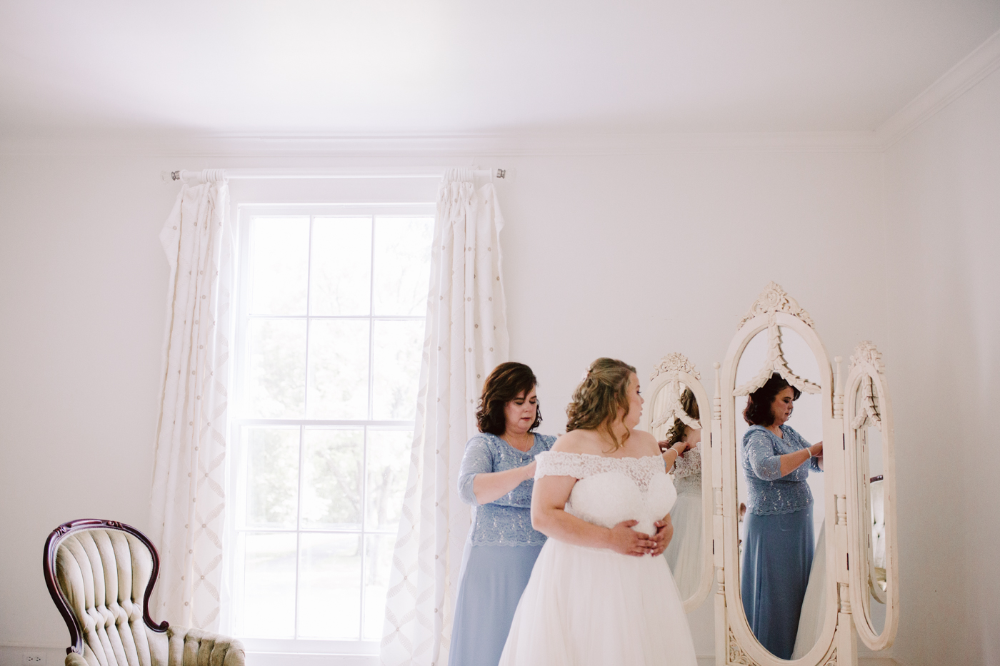 Bride putting on her dress at sunny summer wedding at the venue at twin oaks in tennessee
