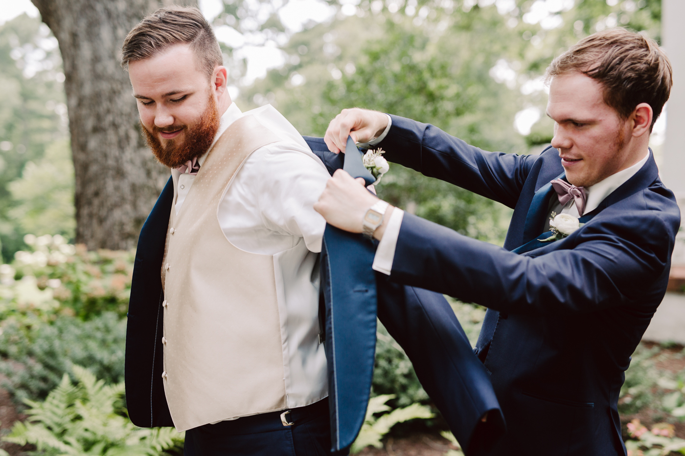 Best man helping the groom get ready before a sunny summer wedding at the venue at twin oaks in tennessee