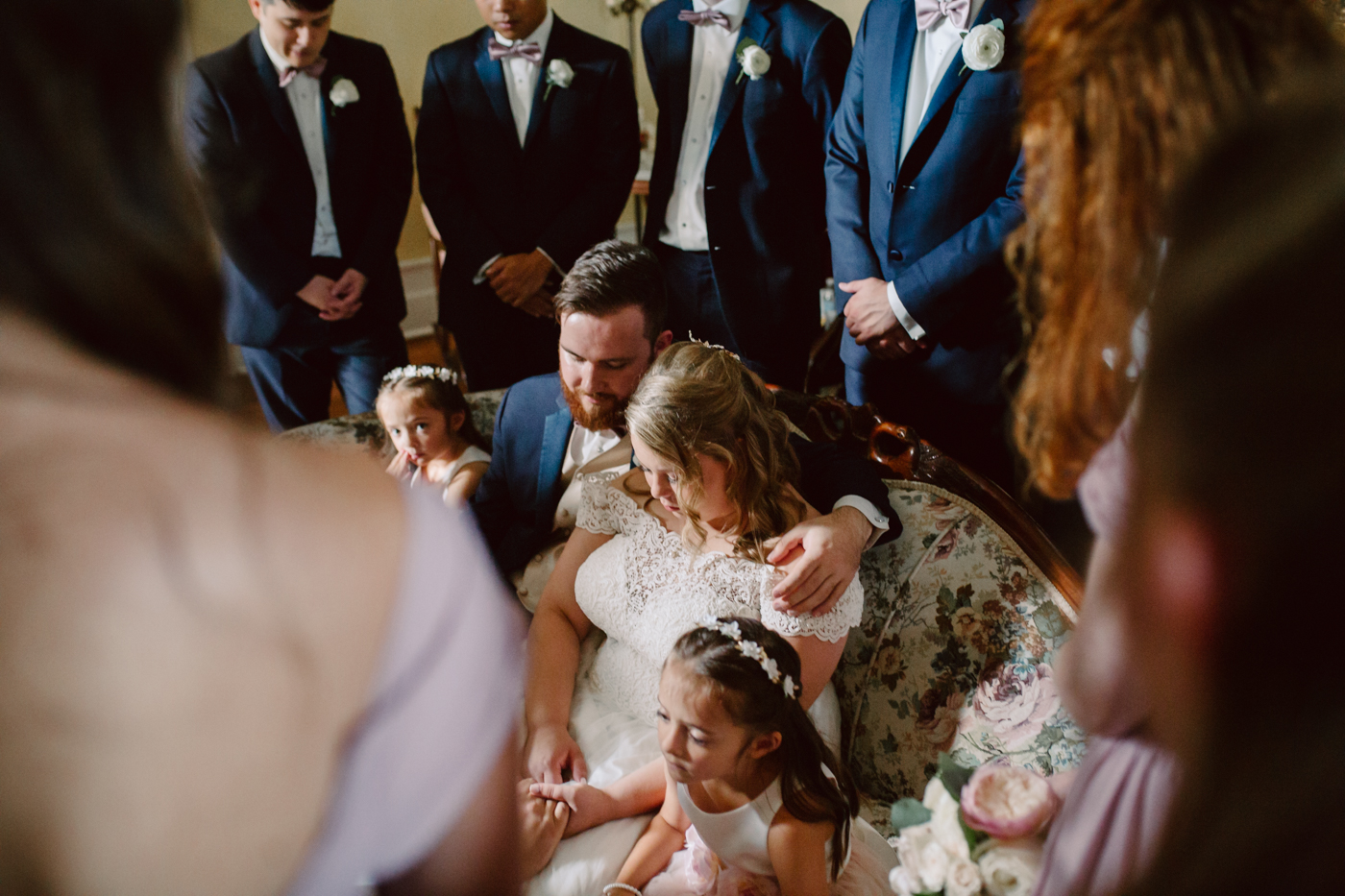 Praying before a sunny summer wedding at the venue at twin oaks tennessee