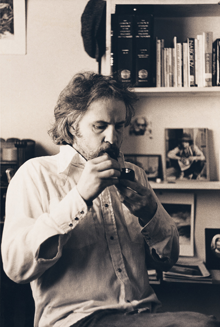 LIGHTING A PIPE IN HIS STUDY, 1975