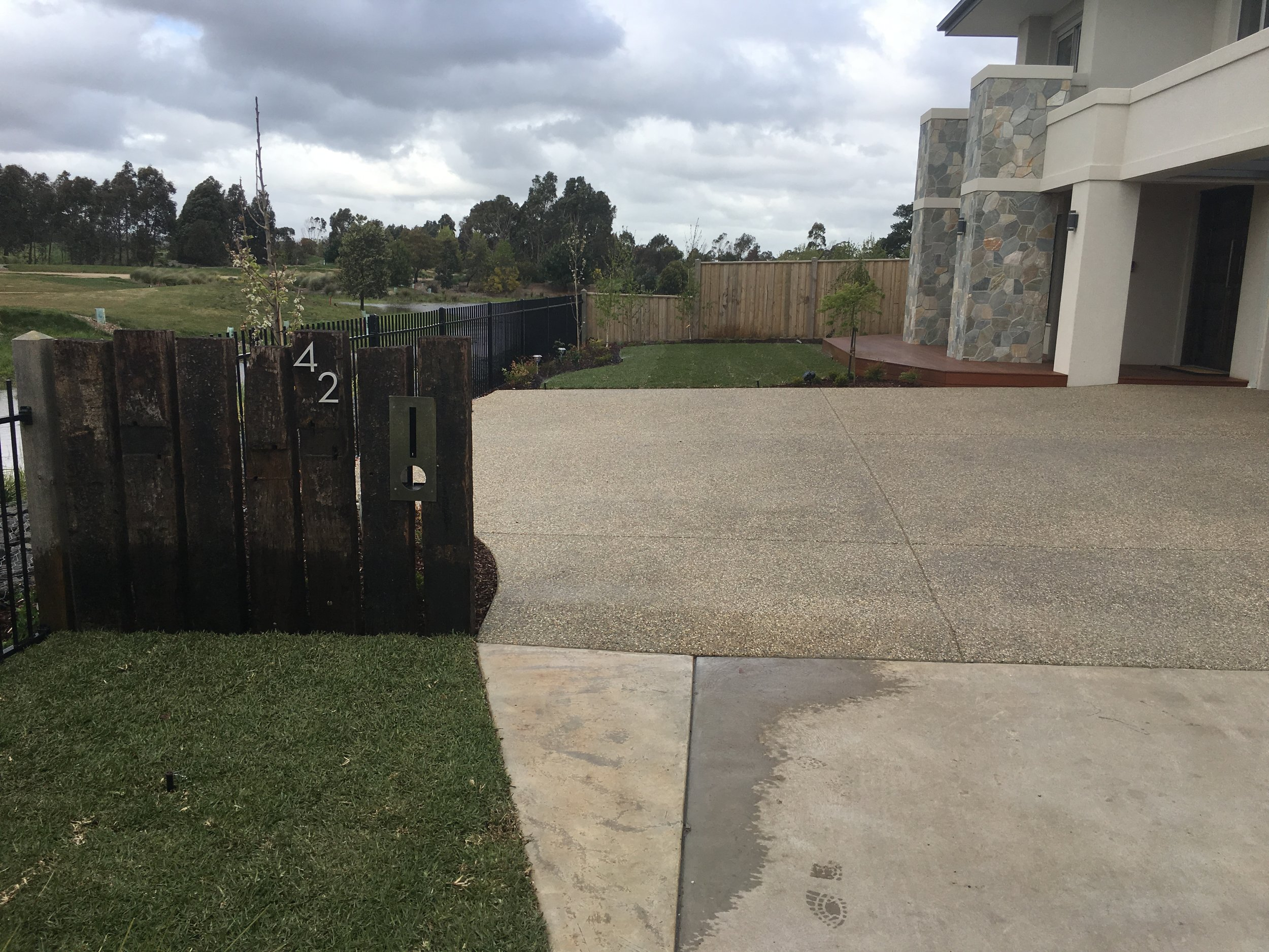 Instant turf, garden bed and old sleeper upright staggered fence with letter box