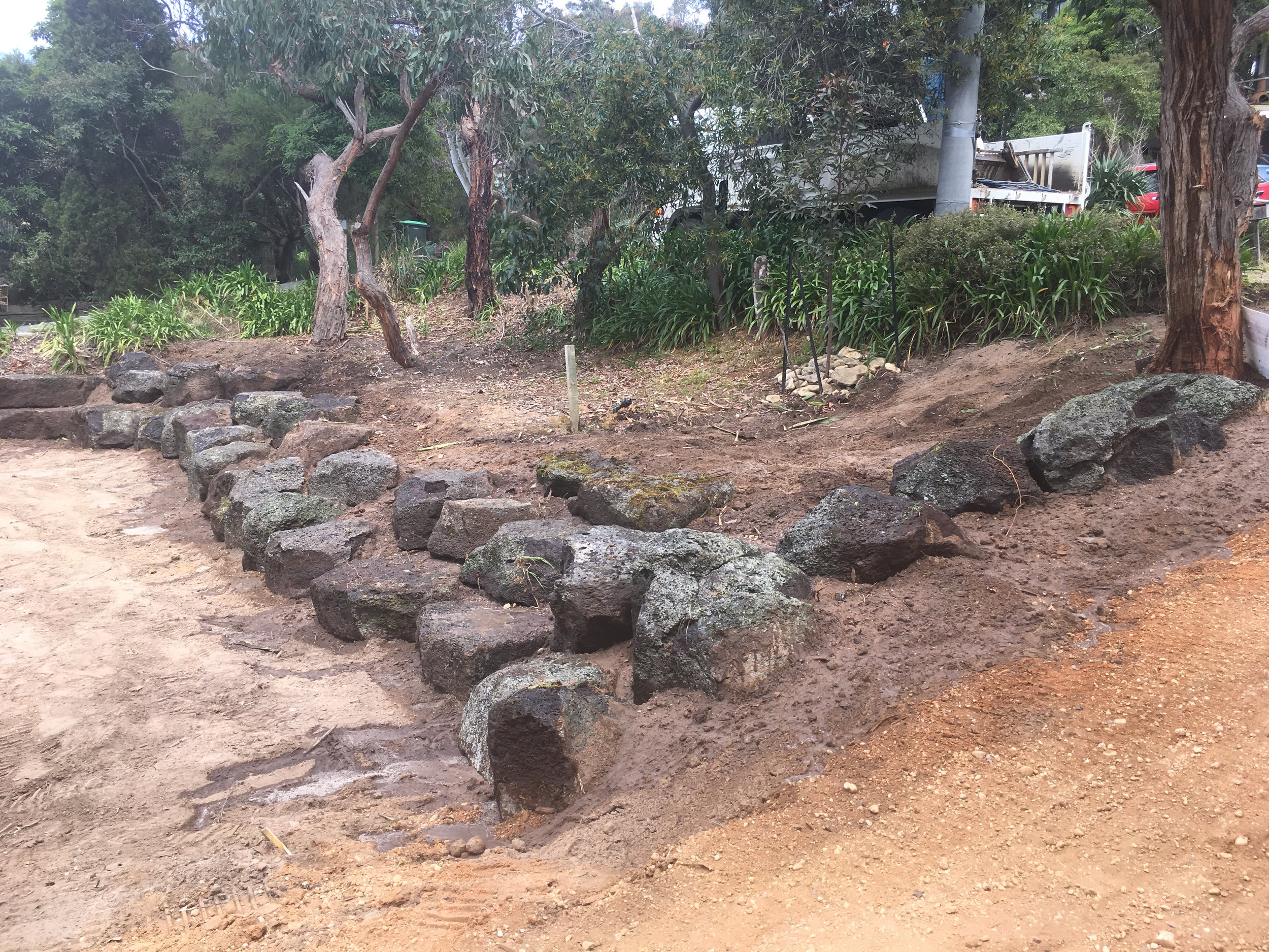Progress shot installing rock retaining wall