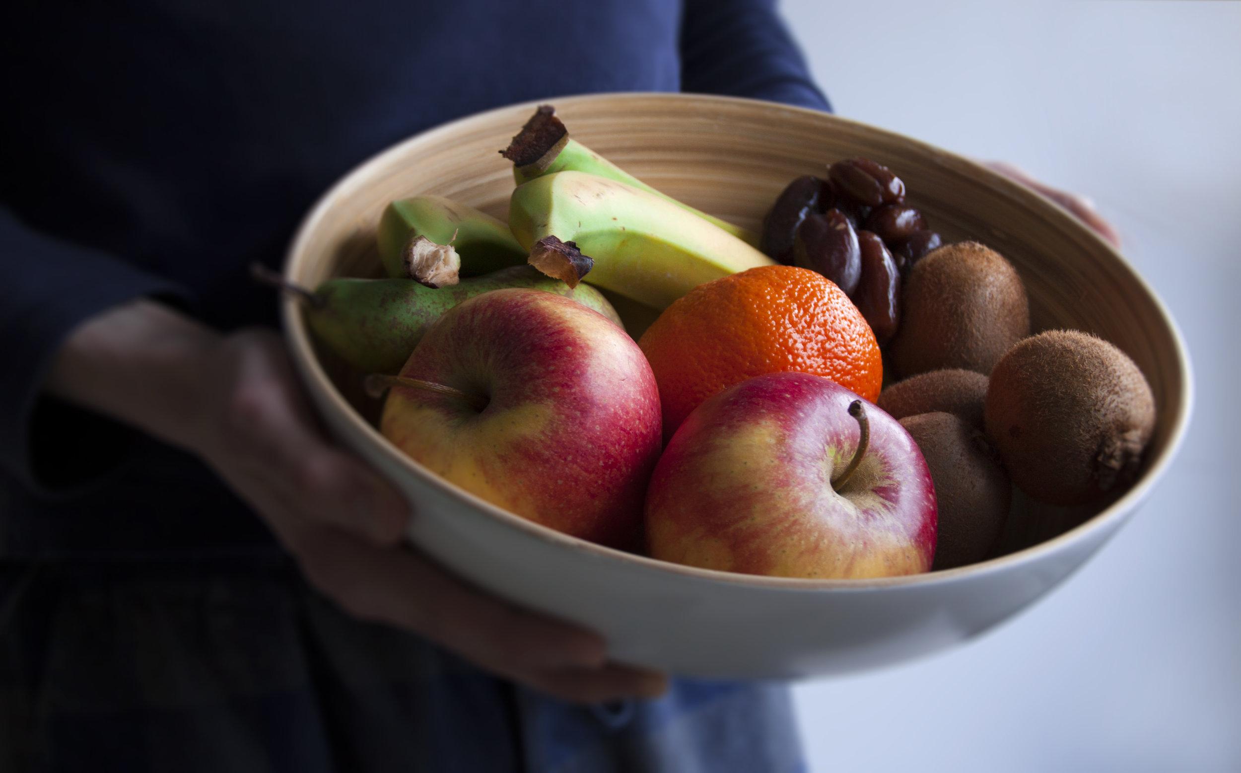 Eén Wildgroeiportie fruit: 3–4 bananen, 2 appels, een peer, een mandora, 3–4 kiwi's en 20 Deglet Nour-dadels.