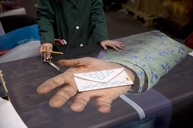 Un angajat în inserție al AFF se pregătește să taie un mesh publicitar.© Kathrin Weident Photography