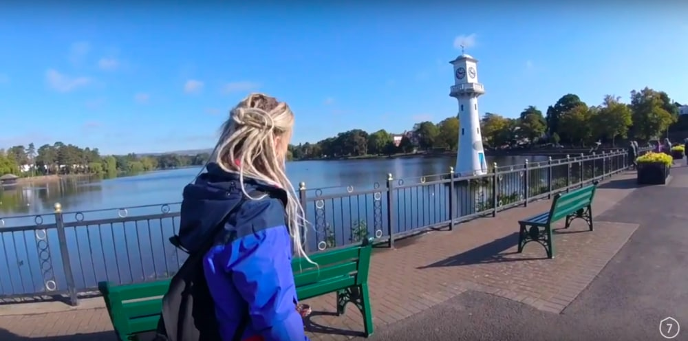 Screenshot taken from Walk of the Week, Roath Park Lake. Beth walking along the promenade with the lighthouse in the background.