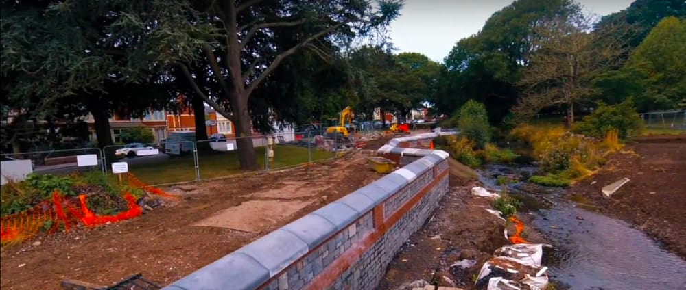 Screenshot taken from Walk of the Week, episode 4: Roath Brook Gardens. Construction taking place at the banks of Roath Brook as a Flood Prevention Scheme implemented by NRW. The stream has been widened and embankments have been built.