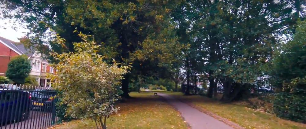 Screenshot taken from Walk of the Week, episode 4: Roath Brook Gardens. As you enter Roath Brook Gardens, you see a path to follow with plenty of trees surrounding you. Roath Brook is to the right, following the direction of the path.