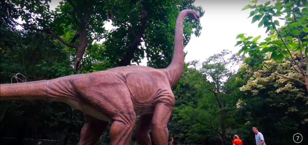 Screenshot taken from Walk of the Week, ep 5. Bute Park. A huge dinosaur looms over everyone. These dinosaurs are a kids dream, and they even roar!