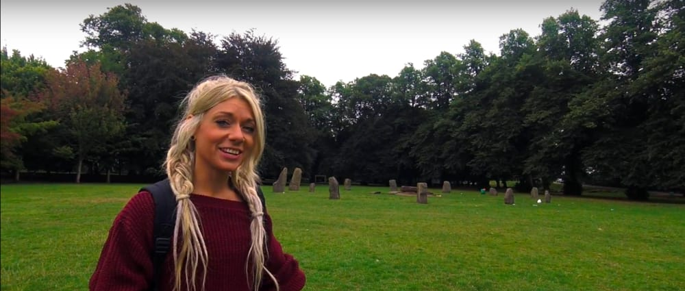 Screenshot taken from Walk of the Week, ep 5. Bute Park. Beth standing in front of the Gorsedd Stones.