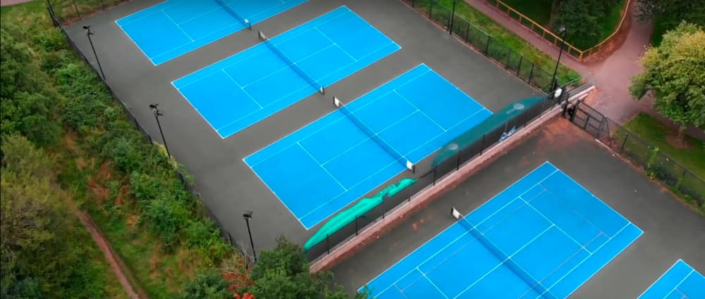 Screenshot taken from Walk of the Week, Heath Park episode. Blue Tennis courts as seen from a drone.