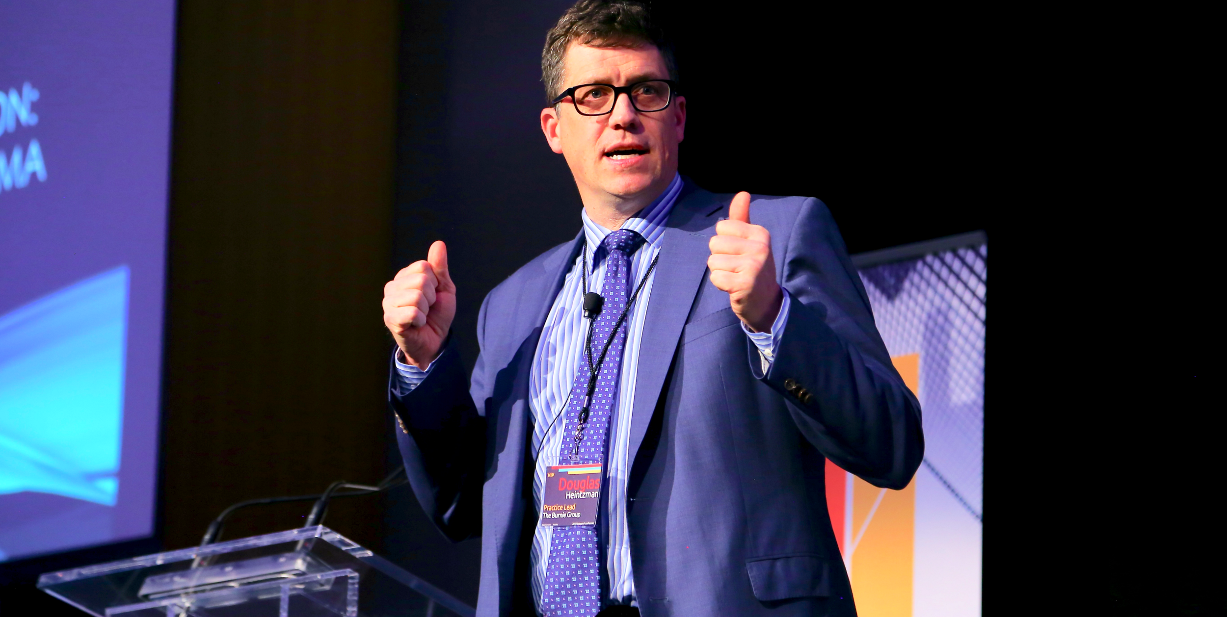 "Douglas Heintzman delivering a keyn ote, ""   Living in an Age of Disruption   "", at the 2018 Analytics By Design conference."