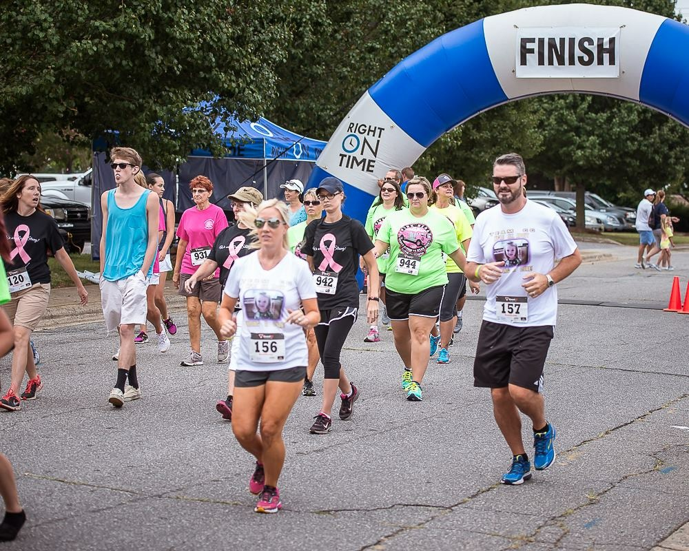 Tom Houck, owner of Thomas Construction Consulting, finishes a marathon to raise money against childhood cancer.