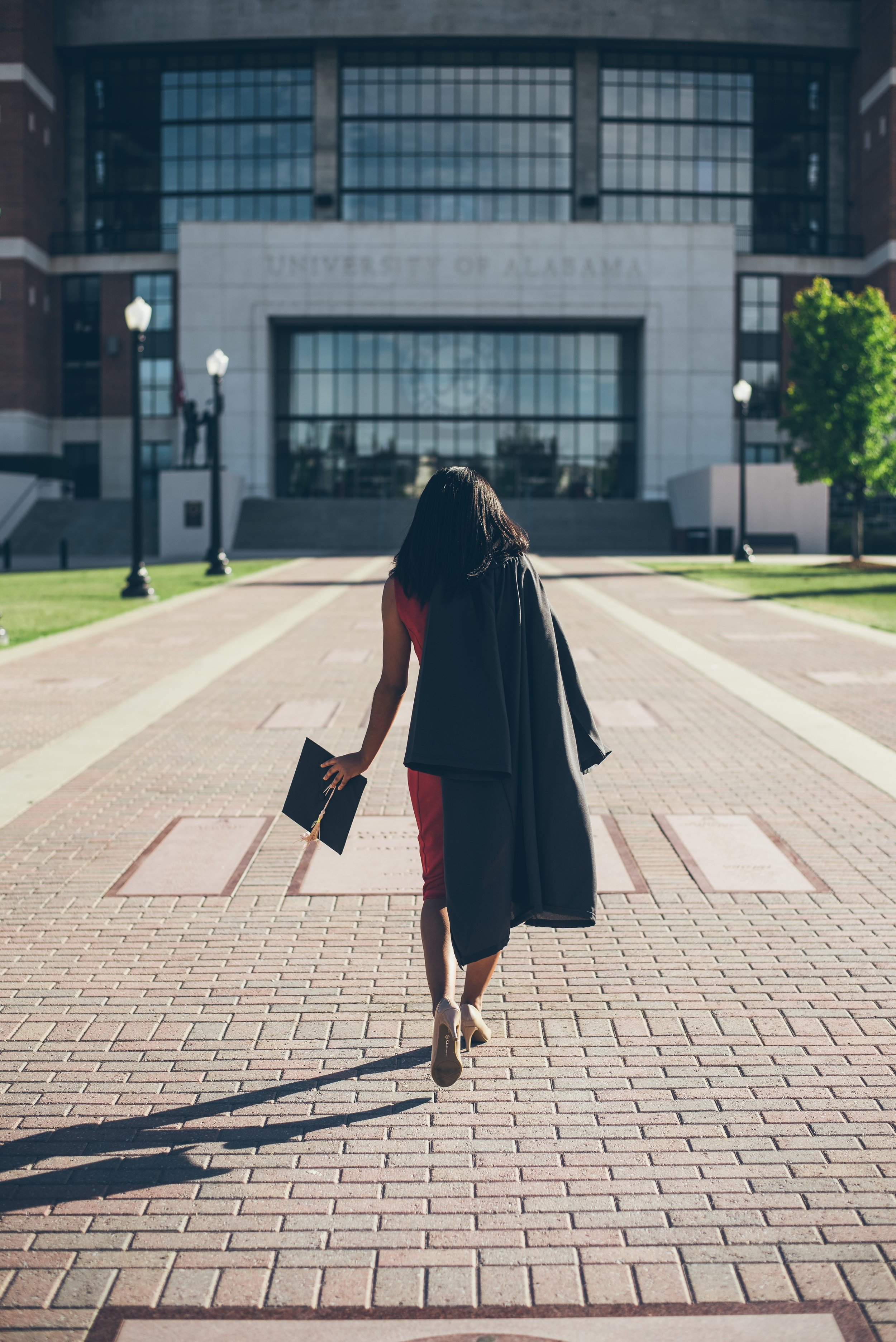 A woman walks away sporting a graduation cap and gown