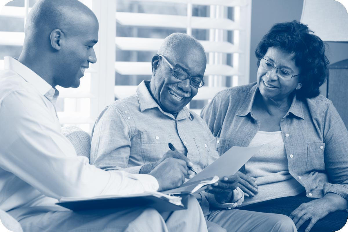 An older couple consults retirement paperwork with a younger man