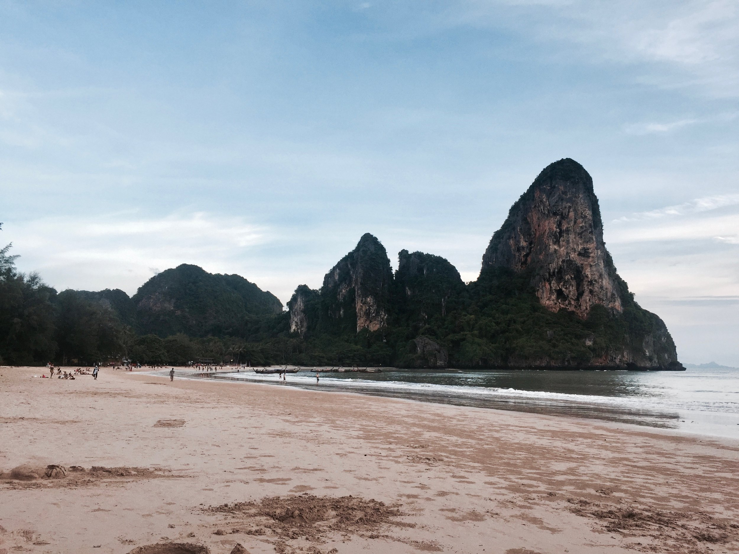 boats in railay, thailand on a summer day with a travel blog