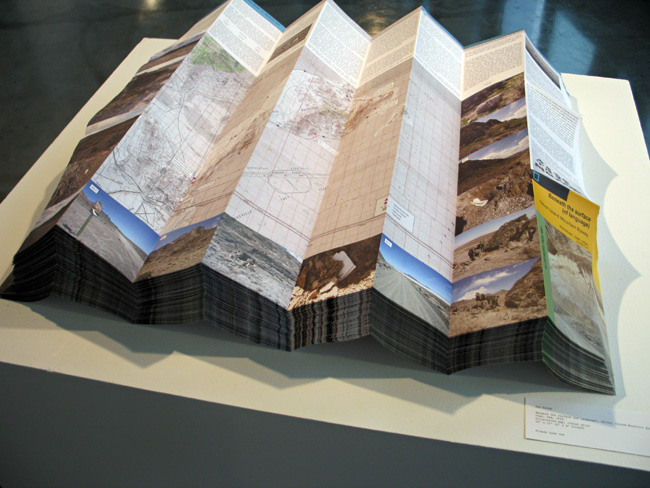 """Installation view of  Beneath the surface (of language), Silver Island Mountain Byway, Wendover, Utah, USA  map stacked as a free give-away in exhibition, """"Claiming Space,"""" Quarter Gallery, University of Minnesota, January to February 2010."""