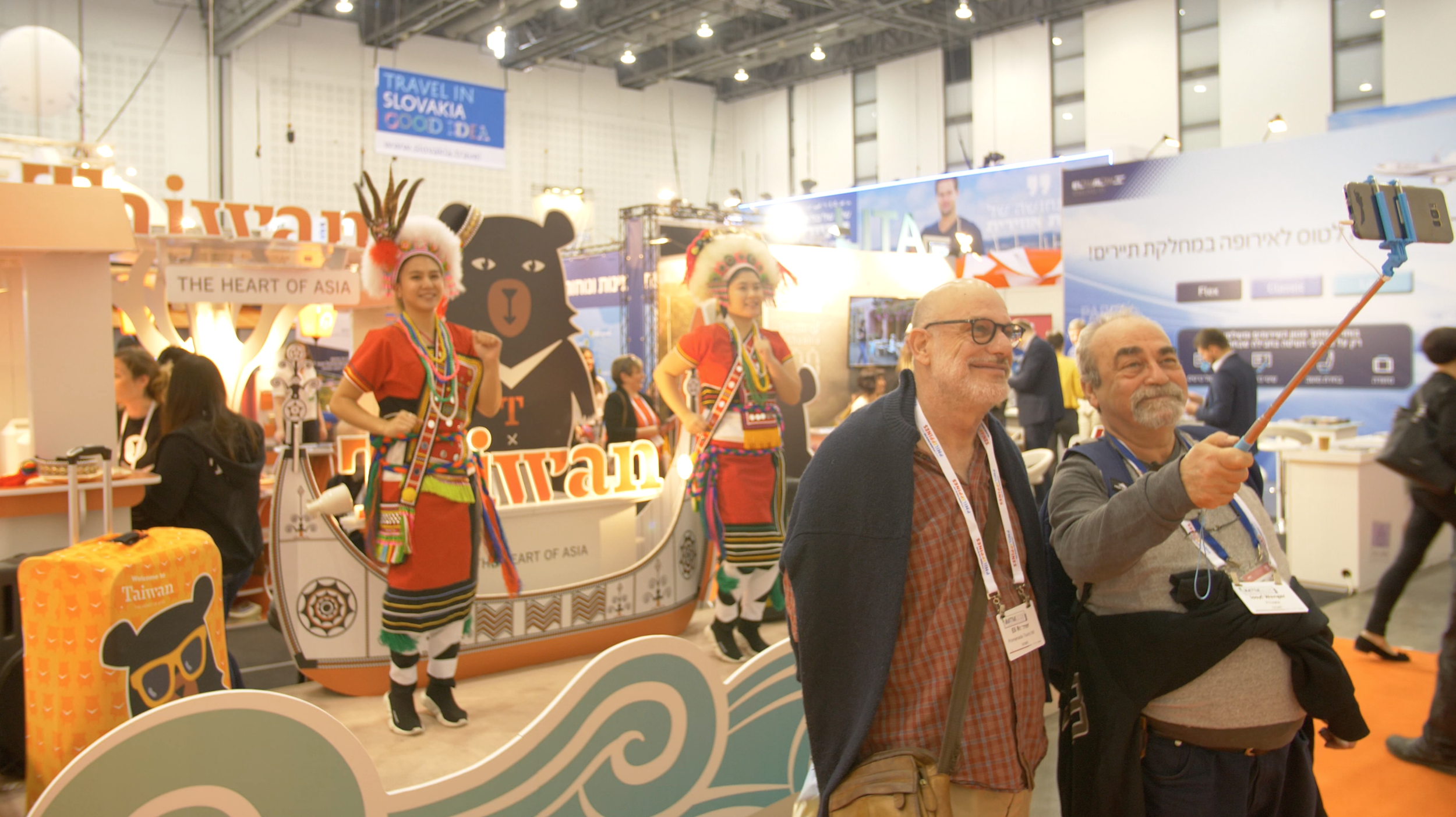 Guests take a selfie in front of Taiwanese aboriginal dancers.png
