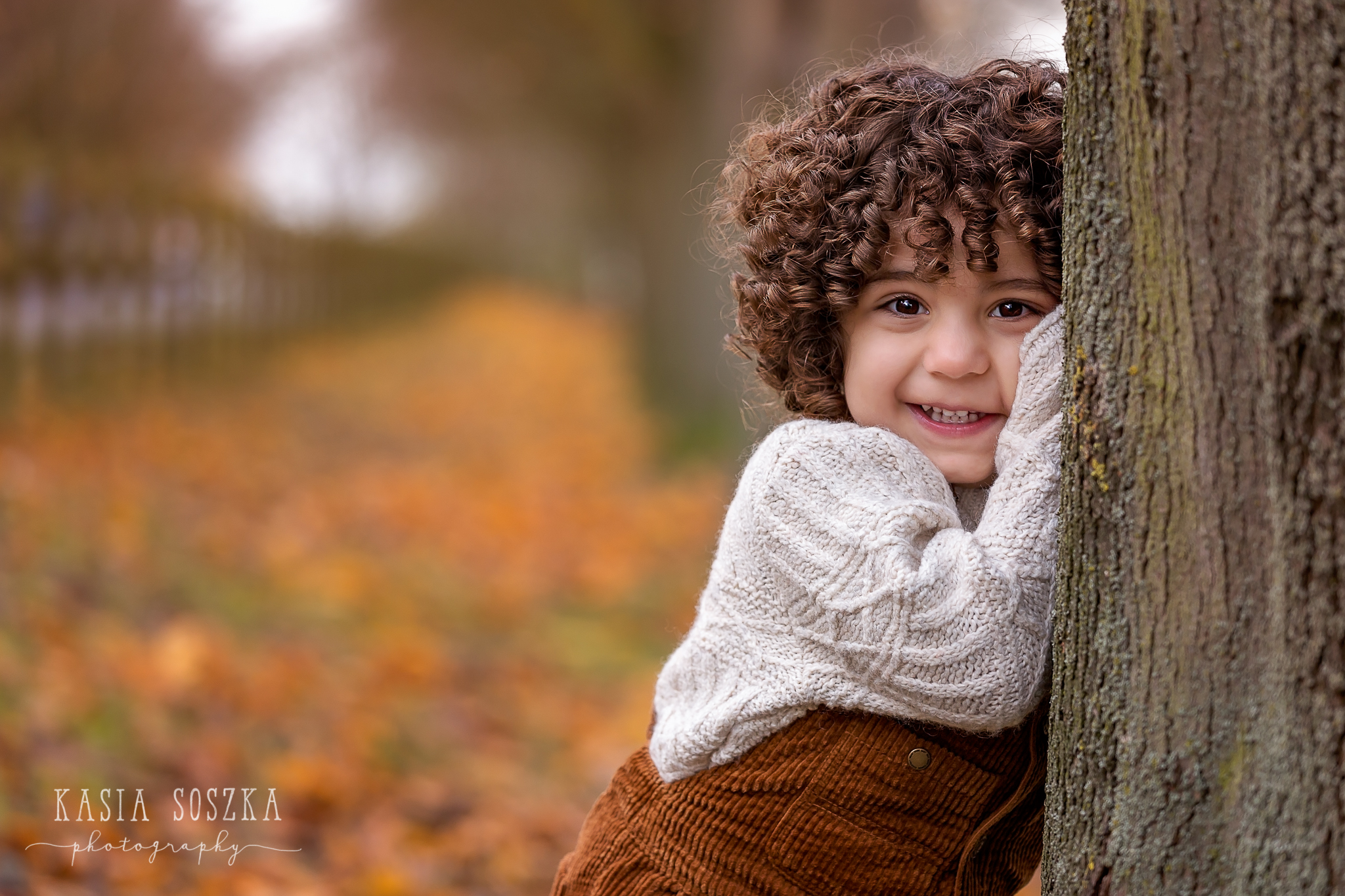 Leeds child photography: little boy with thick curly hair leaning against tree on a beautiful Autumn day.