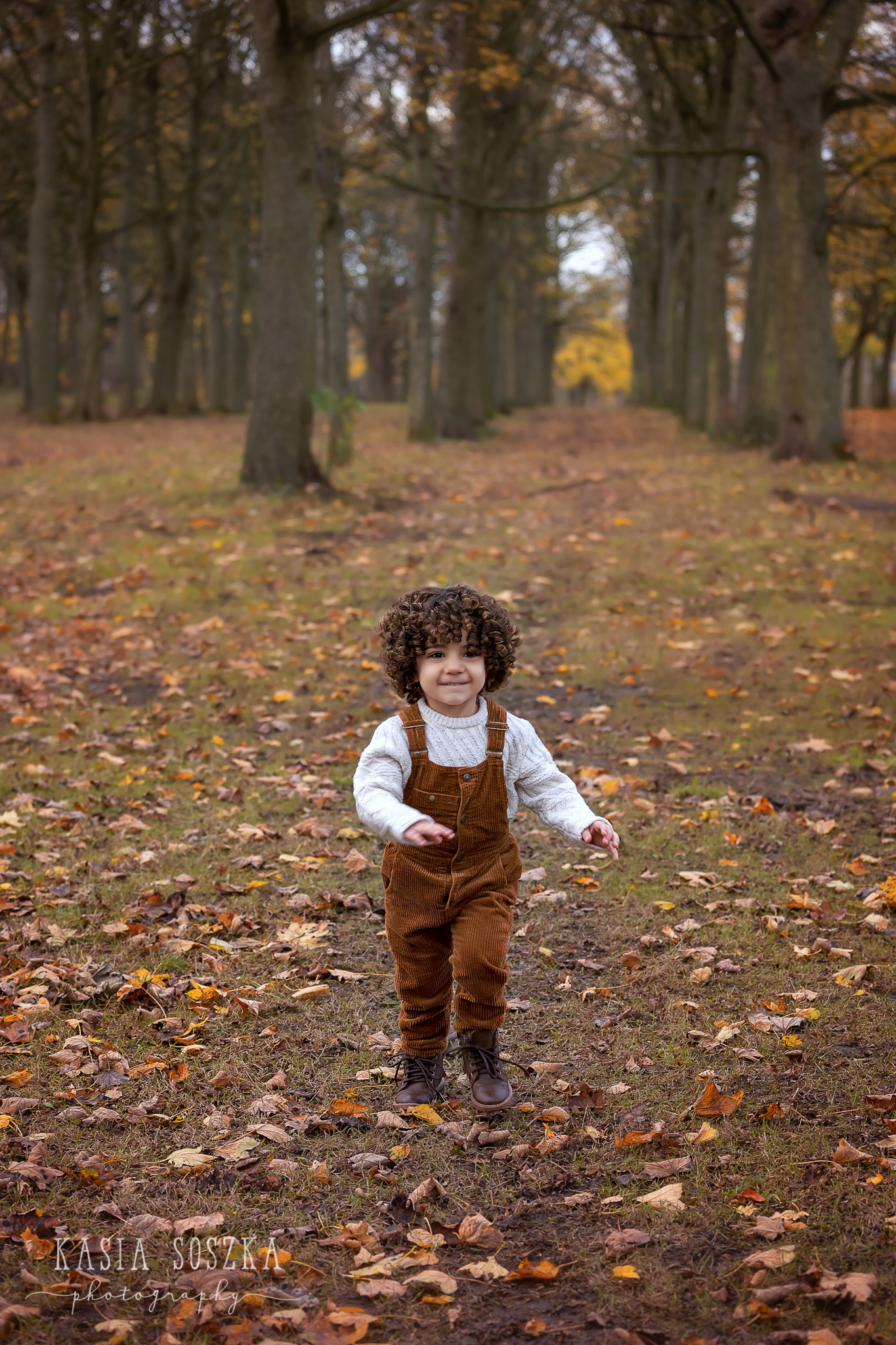 Yorkshire child photography: cute little boy in white sweater and brown dungarees running through a park covered in Autumn leaves.