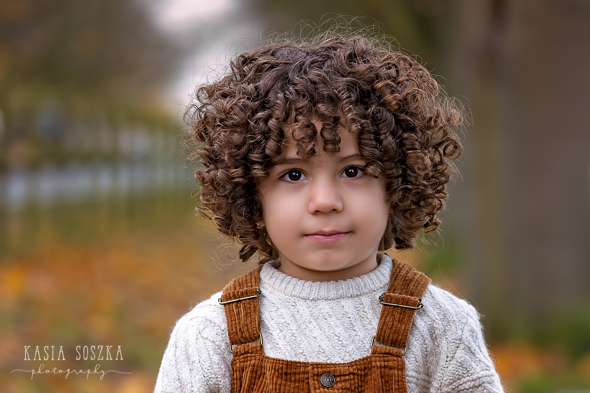 Leeds outdoor child session: portrait of a cute little boy with thick dark curly hair.