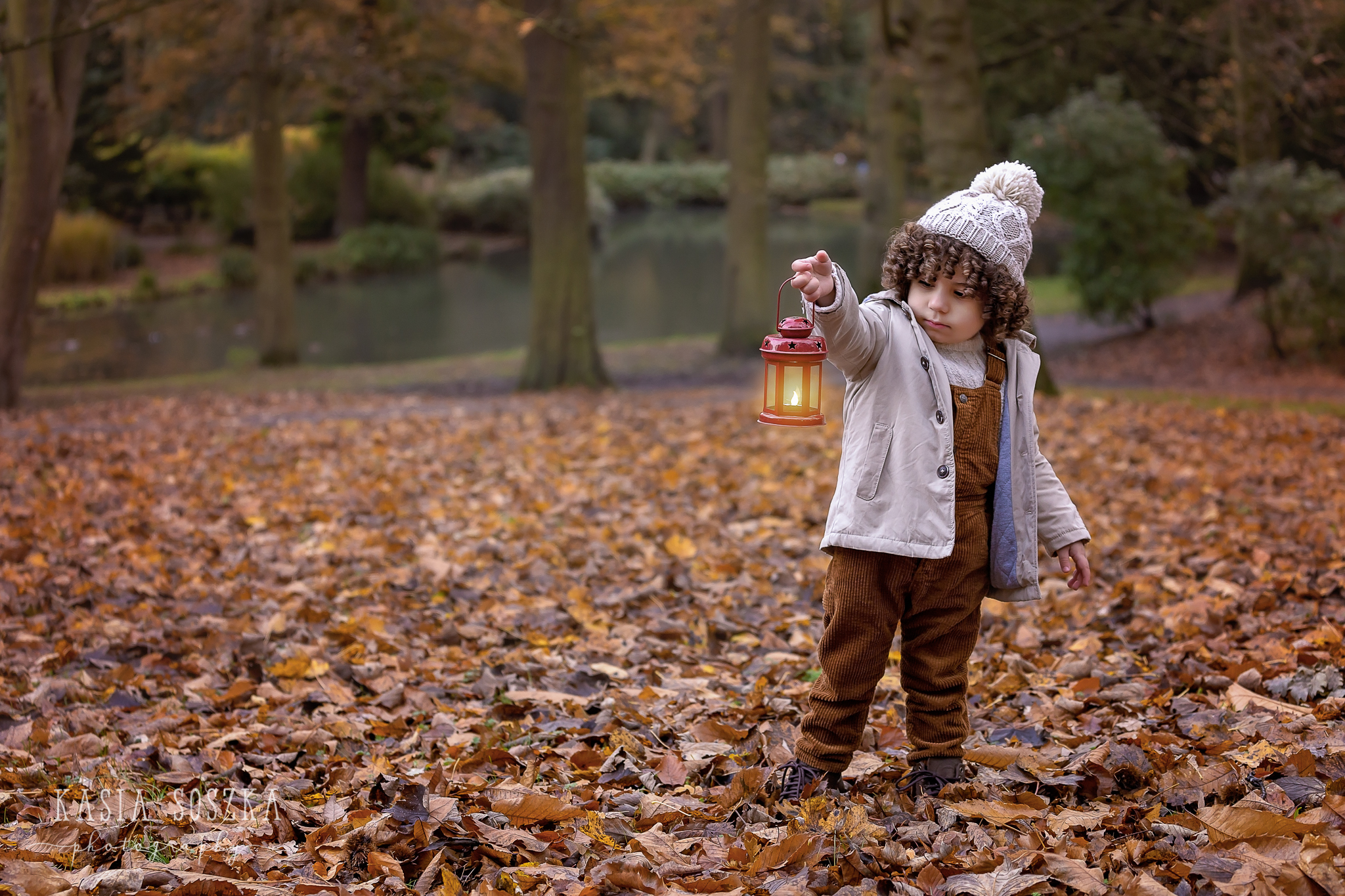 Yorkshire fine art photography: adorable little boy holding a lantern in a park covered in Autumn leaves.