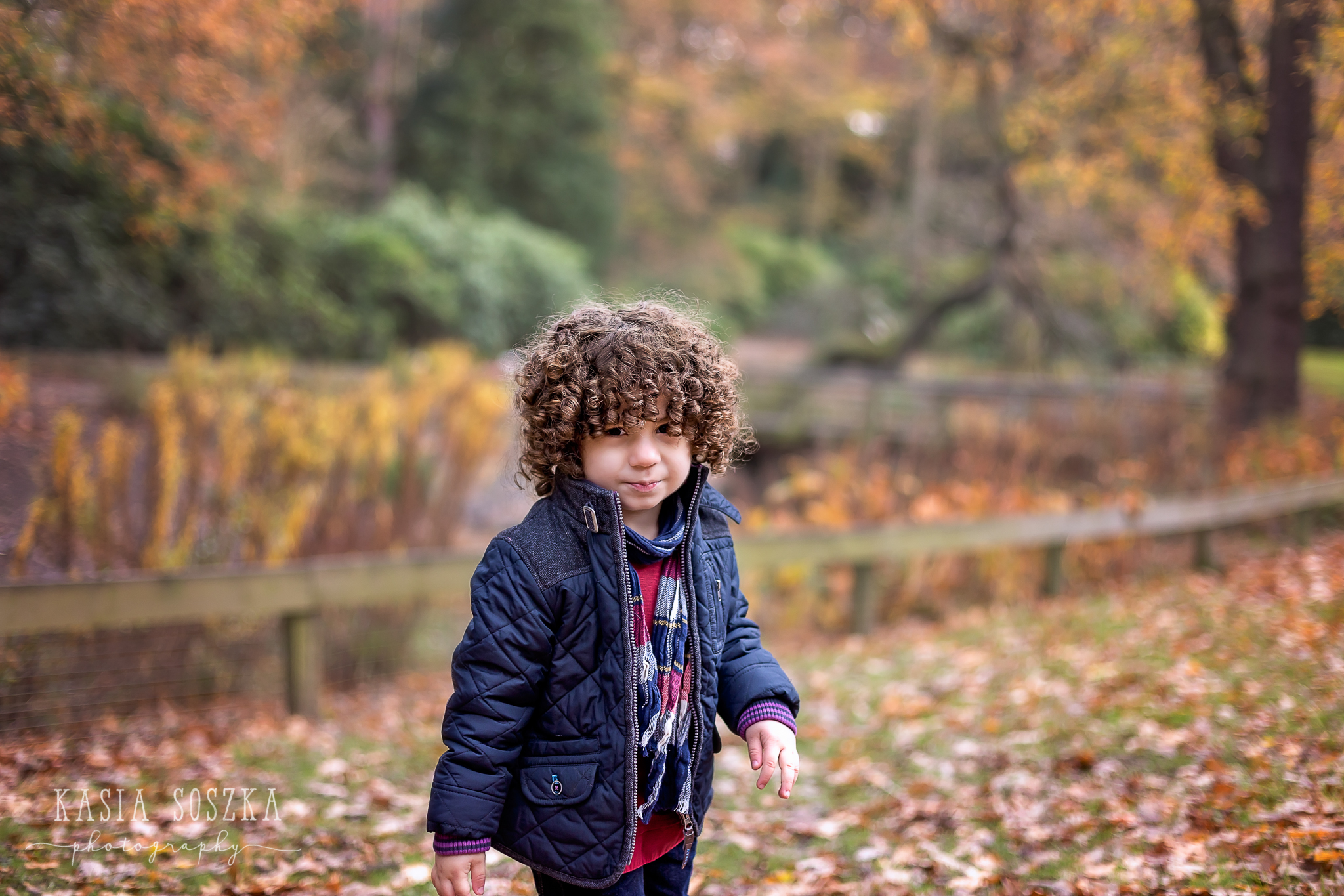 Leeds child photographer: cute little boy with thick dark curly hair walking through a park covered in Autumn leaves.