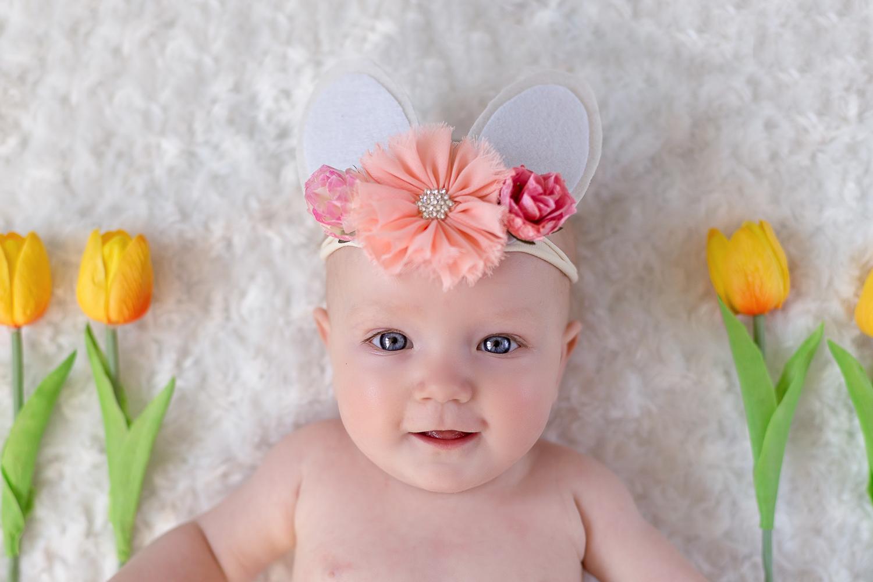 Leeds baby photographer: cute baby girl wearing Easter bunny headband lying on white blanket with yellow tulips