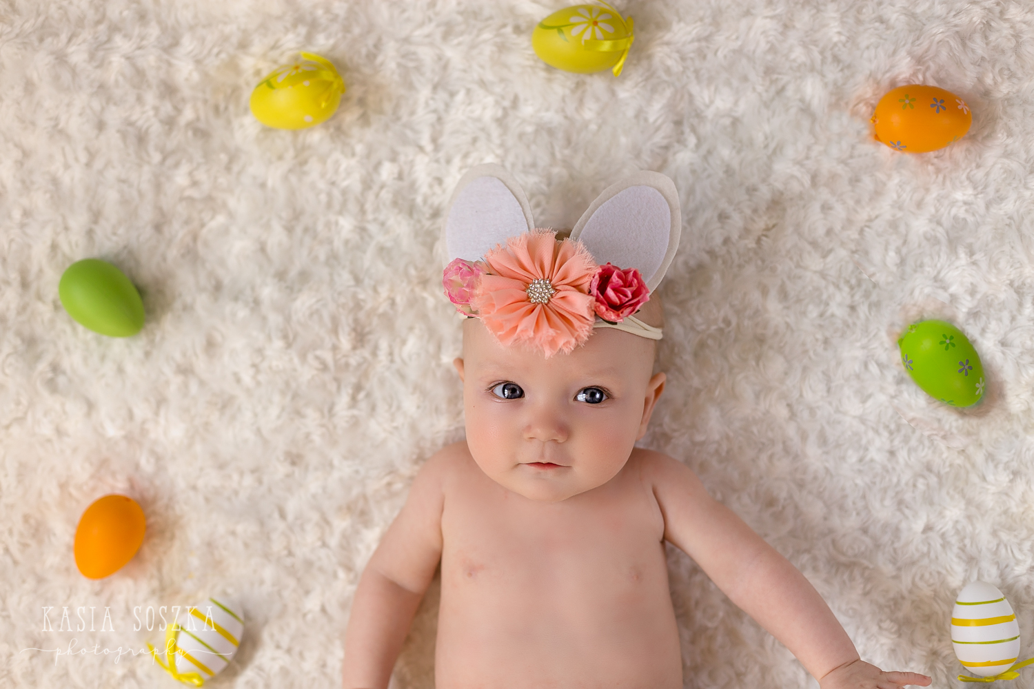 Leeds baby photographer: cute baby girl wearing Easter bunny headband lying on a white blanket in a circle made of colorful Easter Eggs