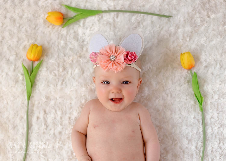 Leeds baby photographer: cute baby girl in Easter bunny headband lying on a white blanket by yellow tulips
