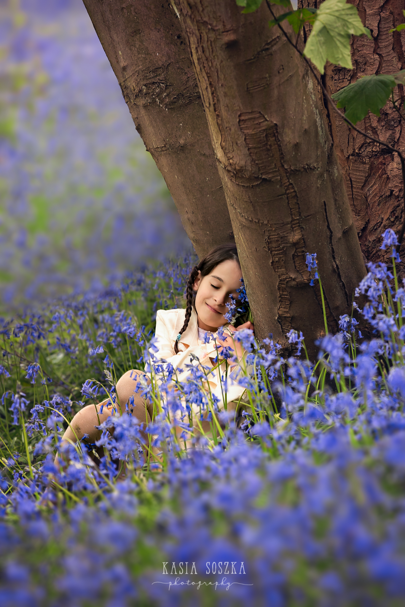 Leeds children photography: little girl sitting by a tree in a bluebell forest