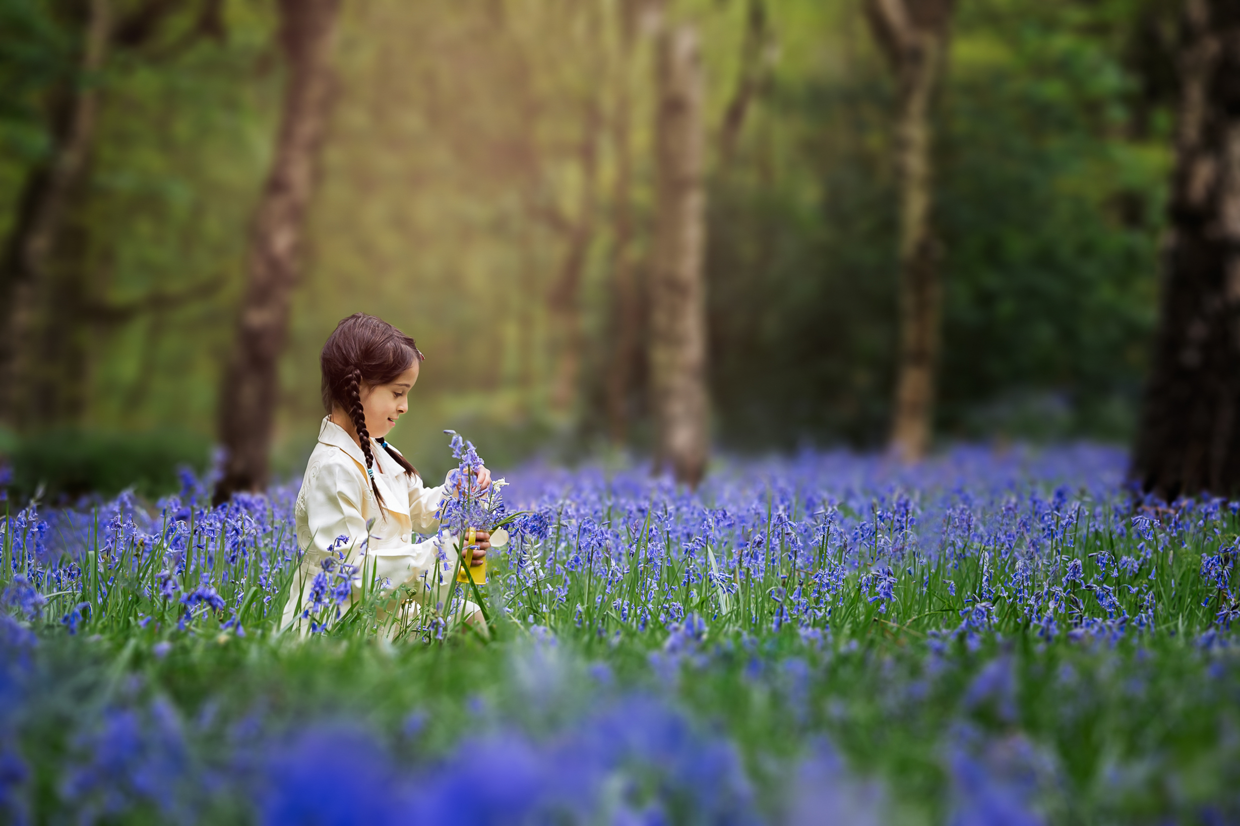 Leeds children photography: little girl sitting in the middle of a bluebell patch