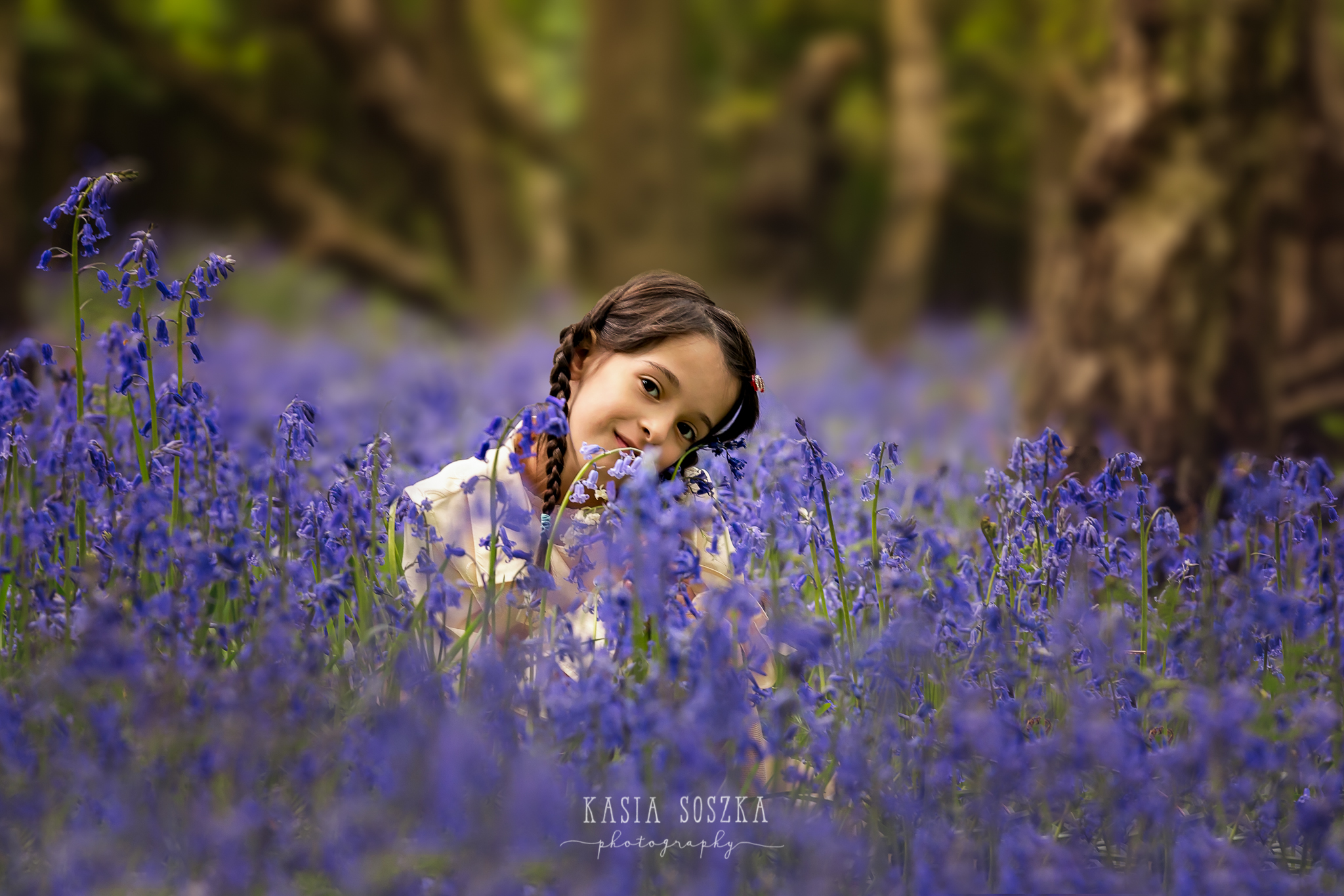 Leeds-bluebell-session: smiling little girl sitting in the middle of bluebell woods.
