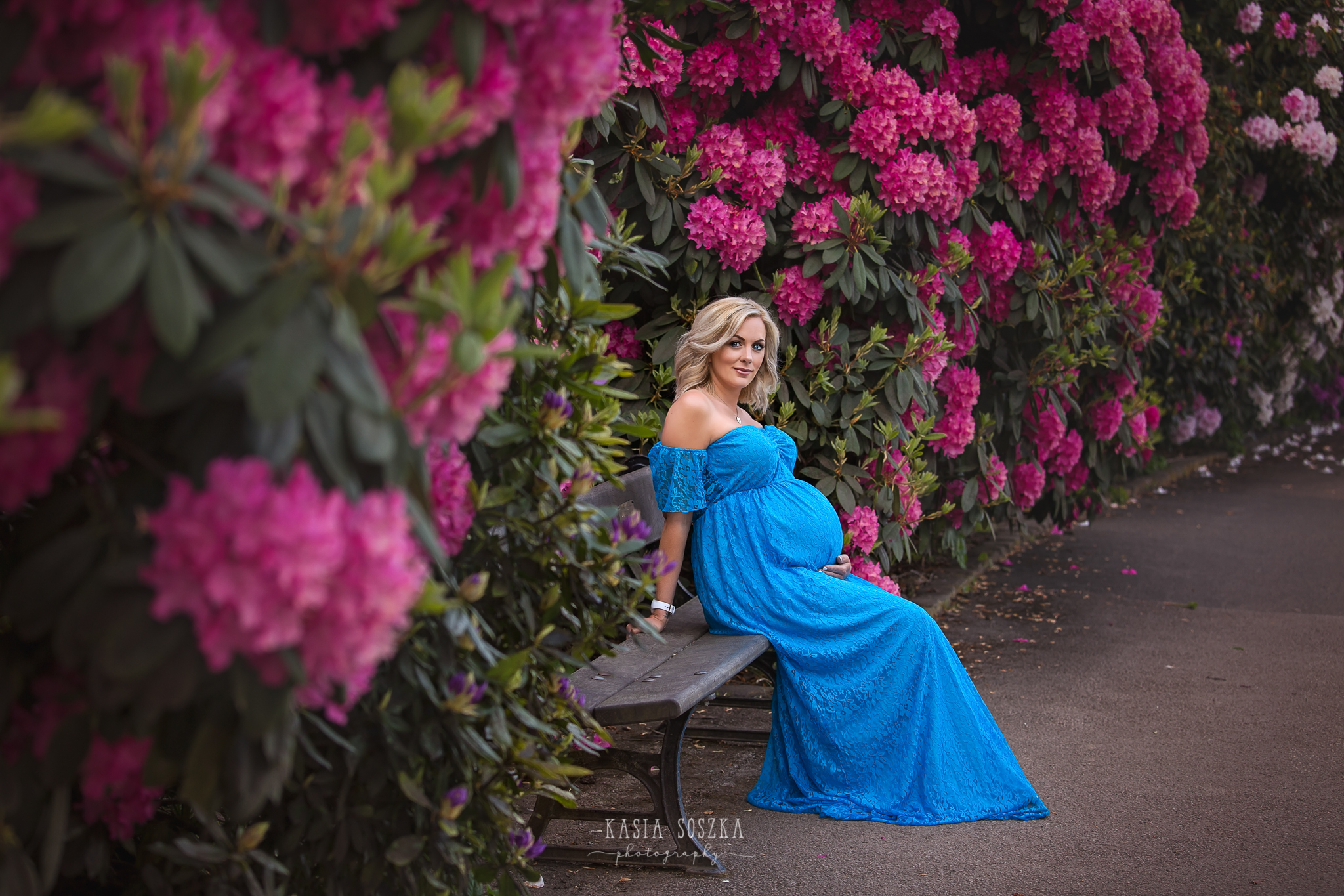 Maternity photography Leeds: beautiful blond pregnant woman in a long blue dress sitting on a bench in a garden full of pink flowers.